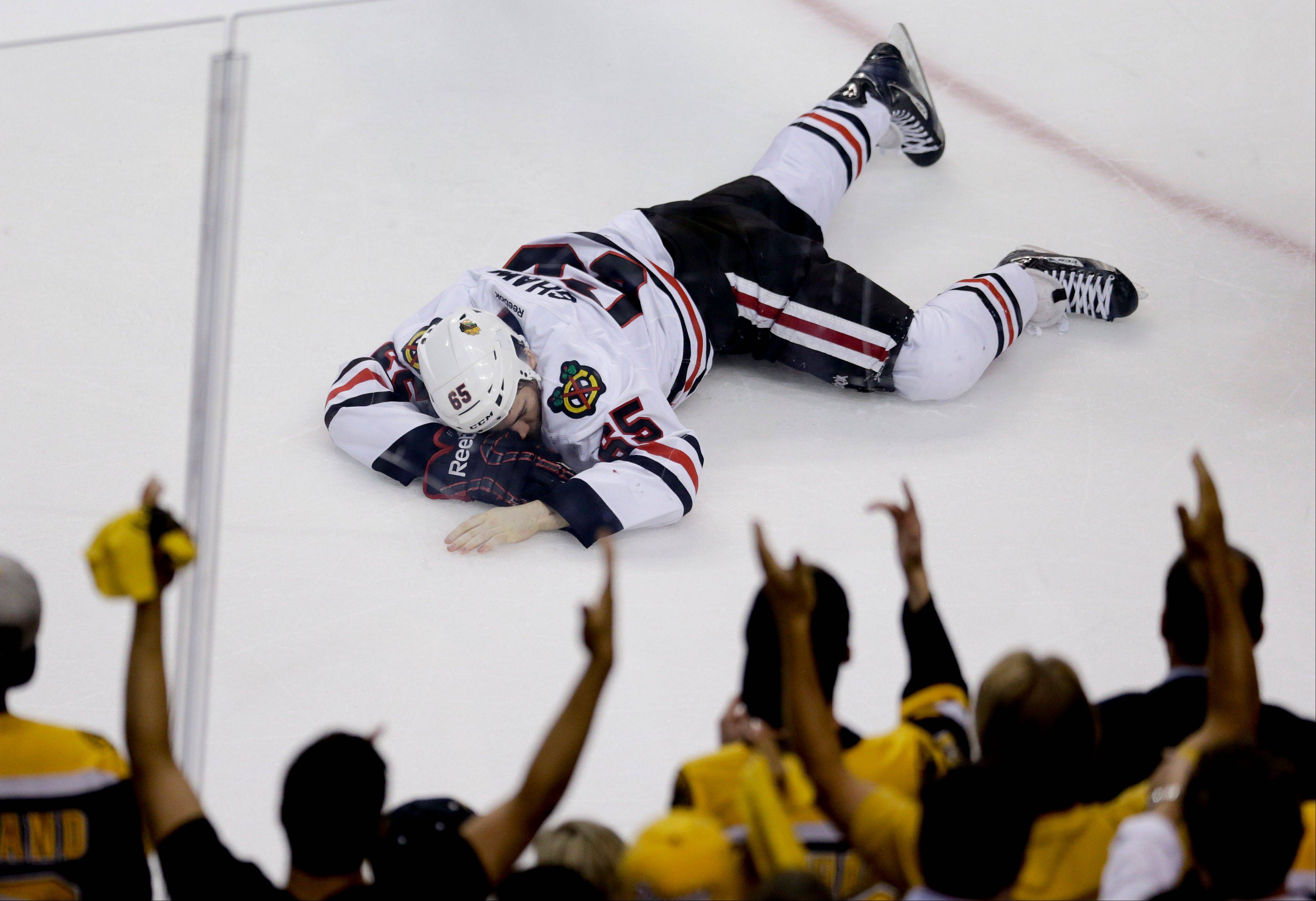 Chicago Blackhawks center Andrew Shaw lays on the ice after taking a puck to the face against the Boston Bruins during the first period in Game 6 of the NHL Stanley Cup Finals, Monday, June 24, 2013, in Boston.