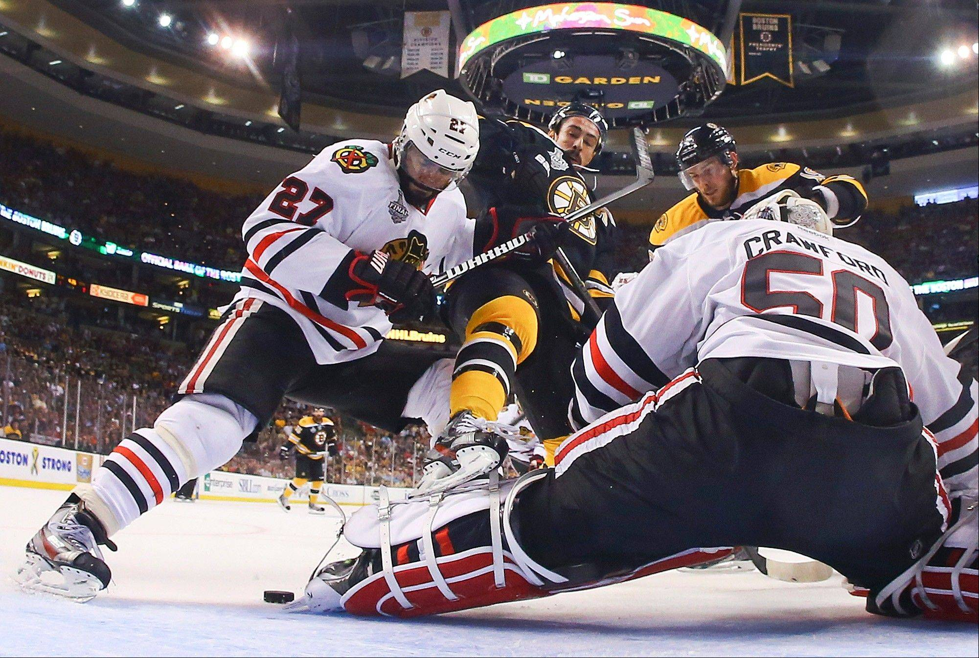 Chicago Blackhawks defenseman Johnny Oduya (27), of Sweden, Boston Bruins centers Chris Kelly (23), and Tyler Seguin (19) fight for position in front of Blackhawks goalie Corey Crawford (50) during the first period in Game 6 of the NHL hockey Stanley Cup Finals.