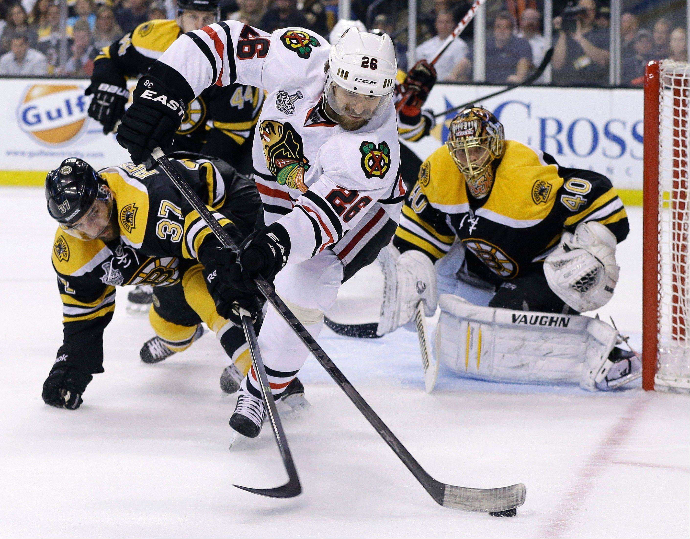 Boston Bruins center Patrice Bergeron (37) and Chicago Blackhawks center Michal Handzus (26), of Slovakia, fight for the puck in front of Boston Bruins goalie Tuukka Rask (40), of Finland, during the first period in Game 6 of the NHL Stanley Cup Finals Monday.