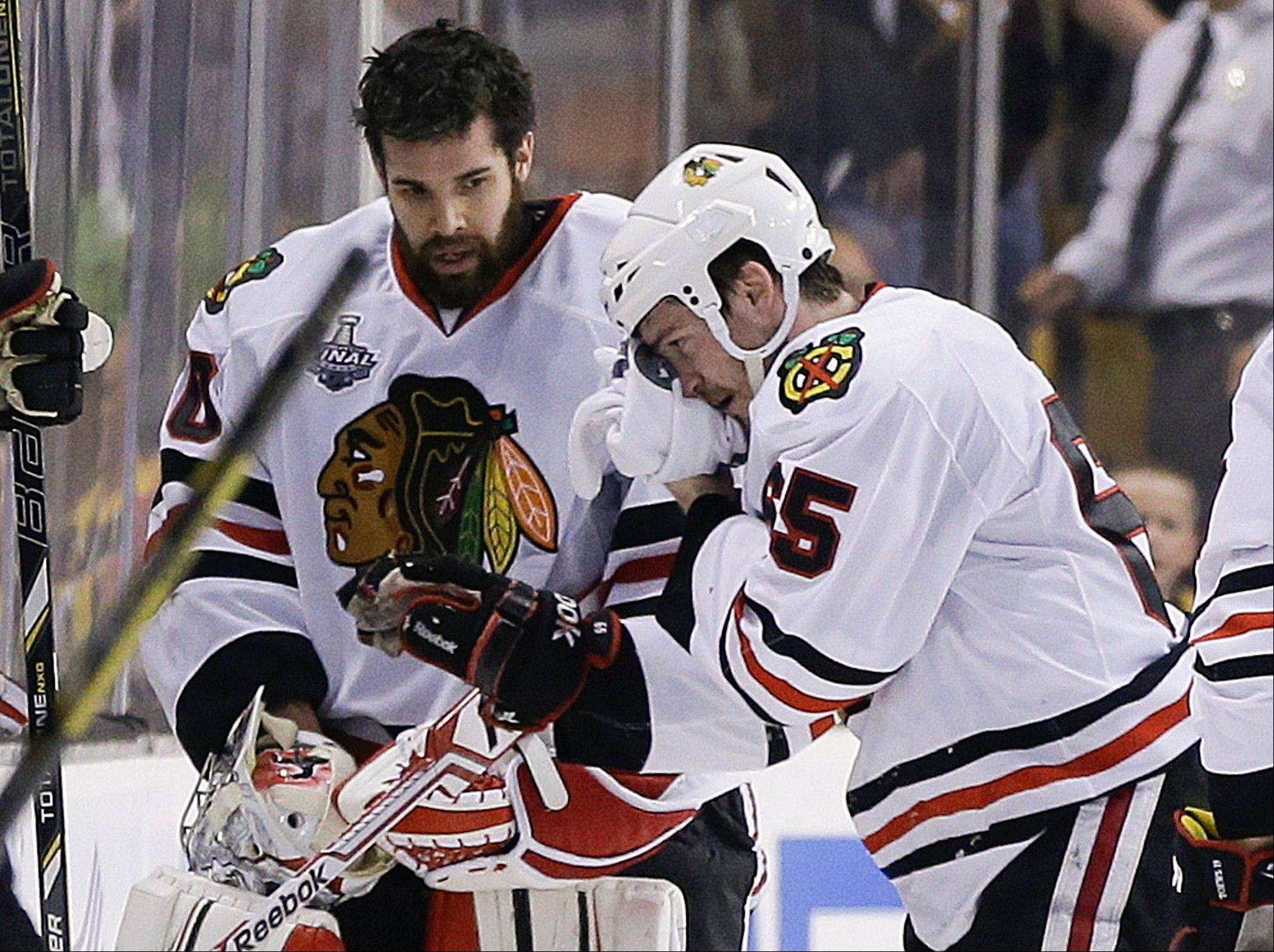Chicago Blackhawks goalie Corey Crawford, left, watches as Chicago Blackhawks center Andrew Shaw (65) skates to the bench after taking a puck to the face against the Boston Bruins during the first period in Game 6 of Stanley Cup Finals Monday.