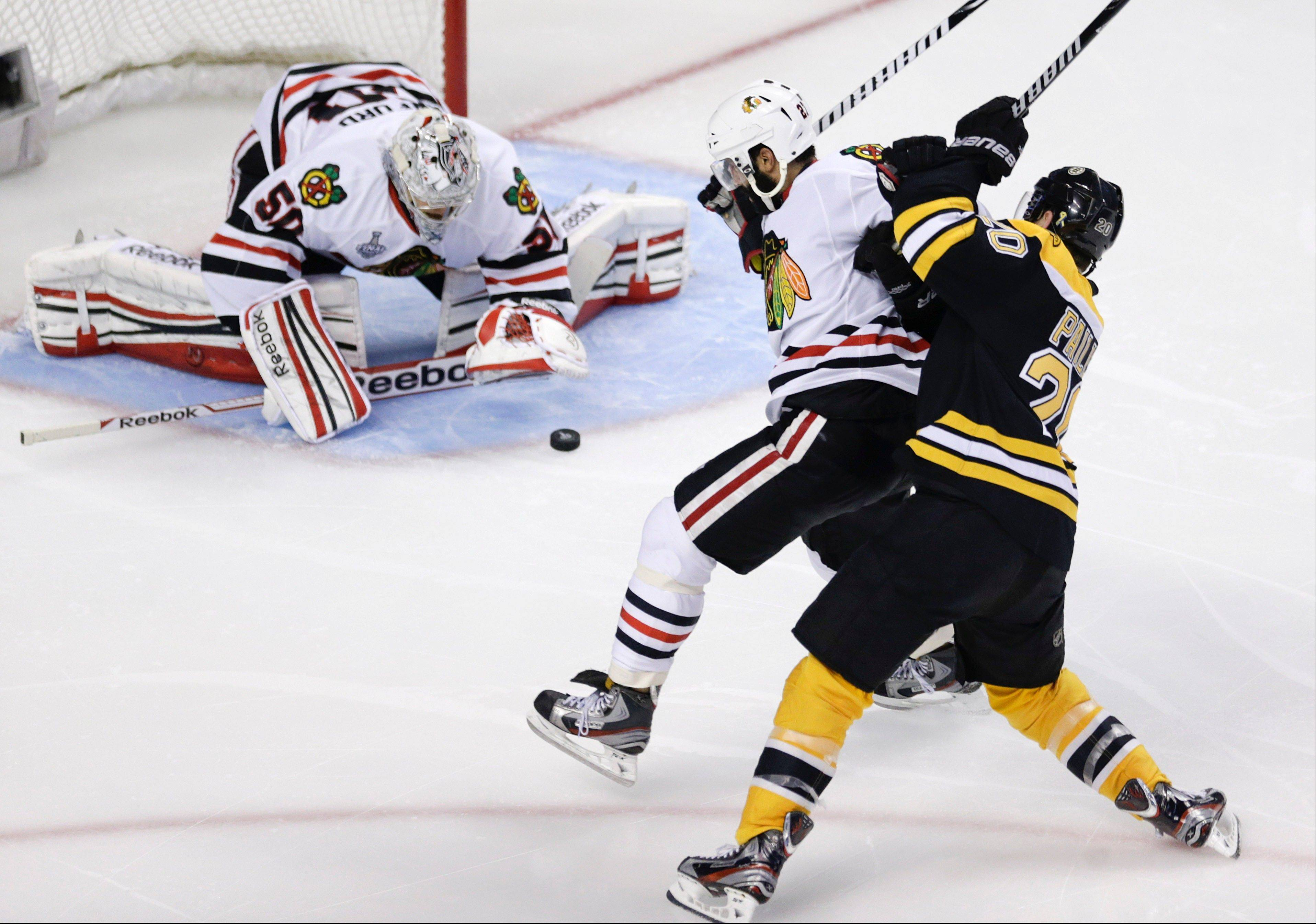 Boston Bruins left wing Daniel Paille (20) ties up Chicago Blackhawks defenseman Johnny Oduya (27), in front of Blackhawks goalie Corey Crawford (50) during the second period in Game 6 of the NHL Stanley Cup Finals Monday in Boston.