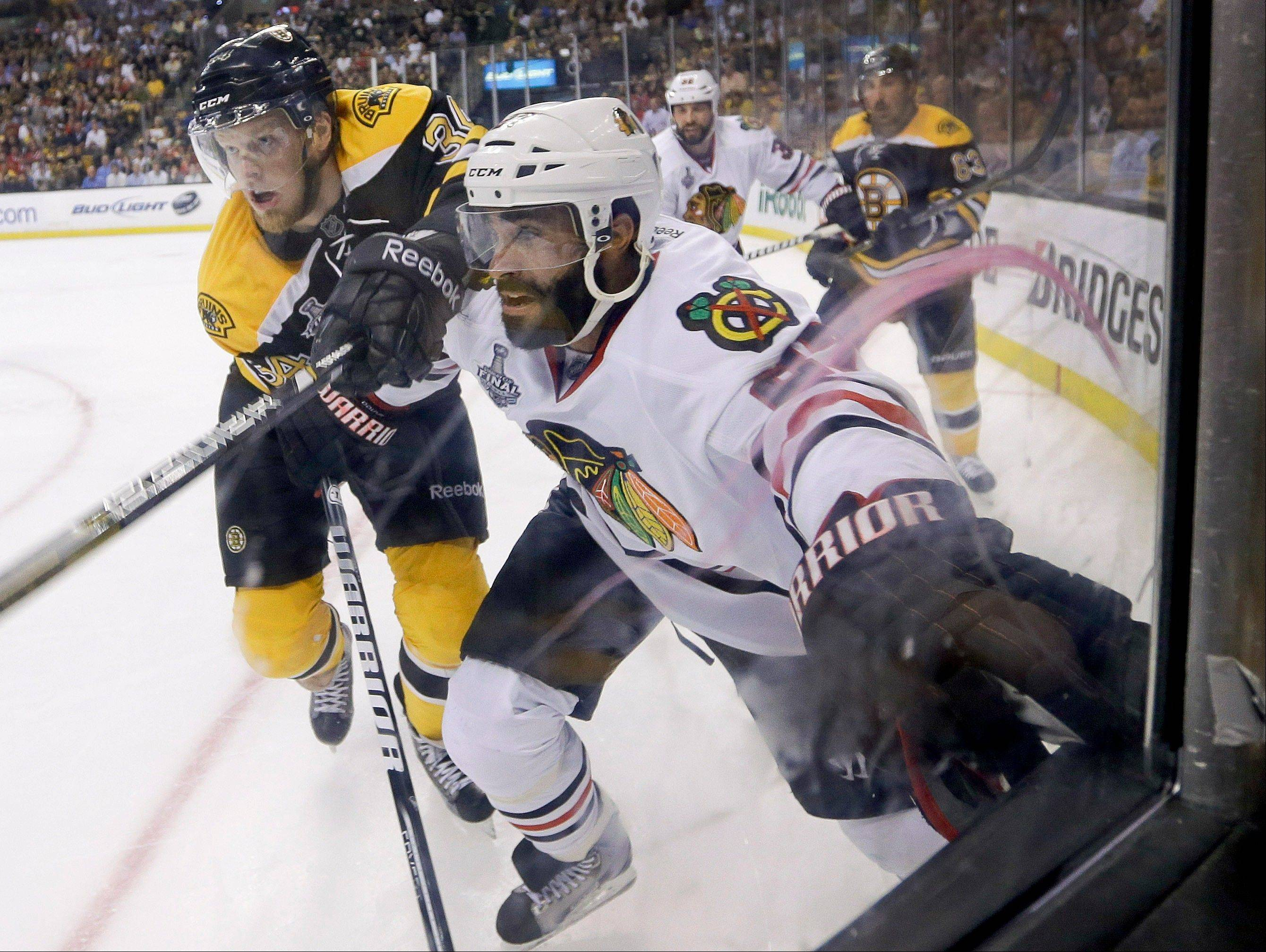 Boston Bruins center Carl Soderberg (34), of Sweden, and Chicago Blackhawks defenseman Johnny Oduya (27), of Sweden, fight for position along the boards during the second period in Game 6 Monday in Boston.