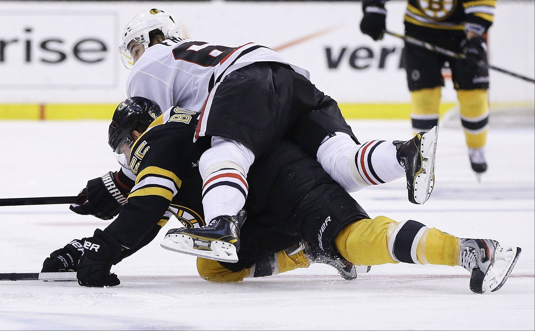 Chicago Blackhawks center Michael Frolik, top, of the Czech Republic, rides down Boston Bruins defenseman Johnny Boychuk (55) during the third period in Game 6 Monday in Boston.