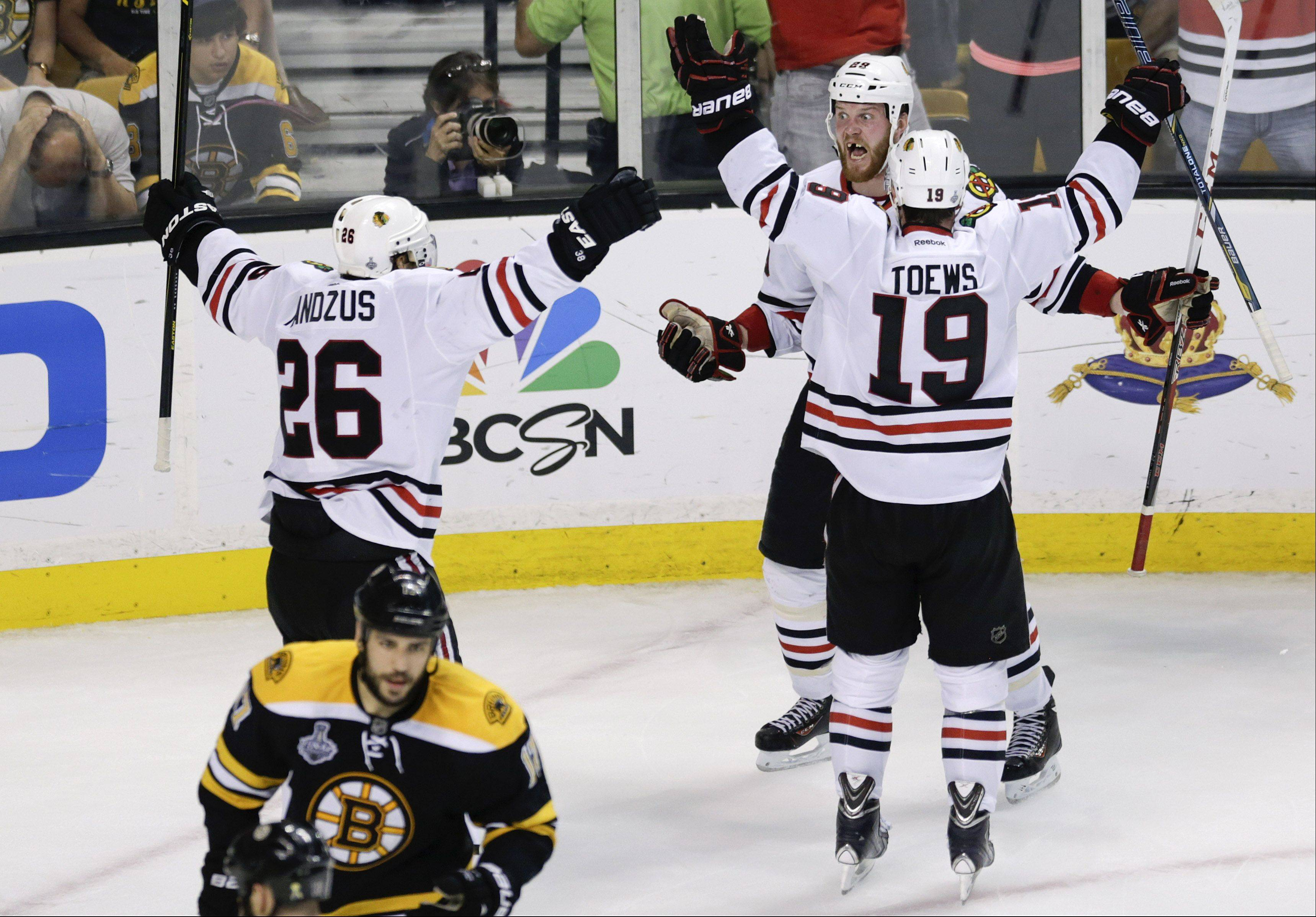 Chicago Blackhawks left wing Bryan Bickell, center, celebrates his goal with center Jonathan Toews (19) and center Michal Handzus (26), of Slovakia, during the third period in Game 6 of the Stanley Cup Finals Monday.