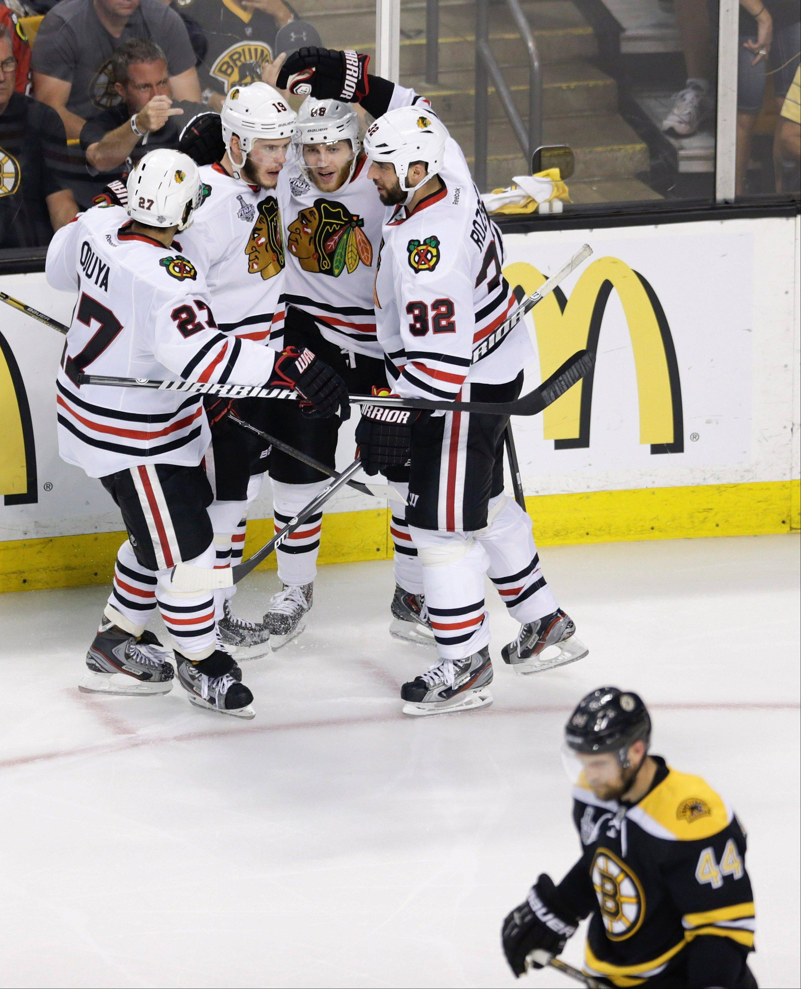 Chicago Blackhawks center Jonathan Toews, left, celebrates his goal against the Boston Bruins with right wing Patrick Kane, center, and defenseman Michal Rozsival (32), of the Czech Republic, during the second period in Game 6 of the Stanley Cup Finals.