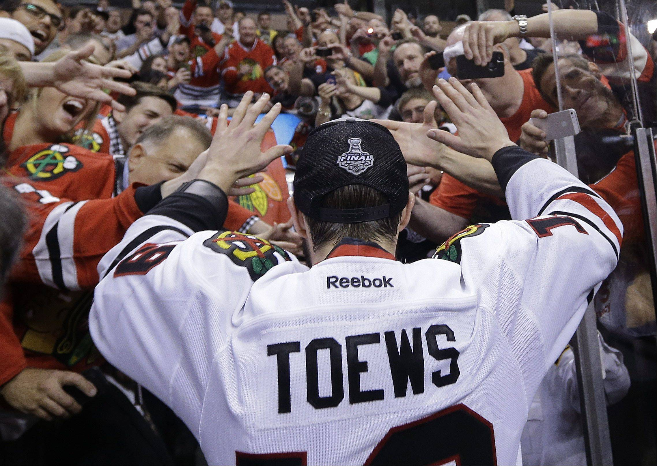 Fans give high-fives to Chicago Blackhawks center Jonathan Toews after the Blackhawks beat the Boston Bruins in Game 6 of the NHL Stanley Cup Finals Monday, June 24, 2013, in Boston.