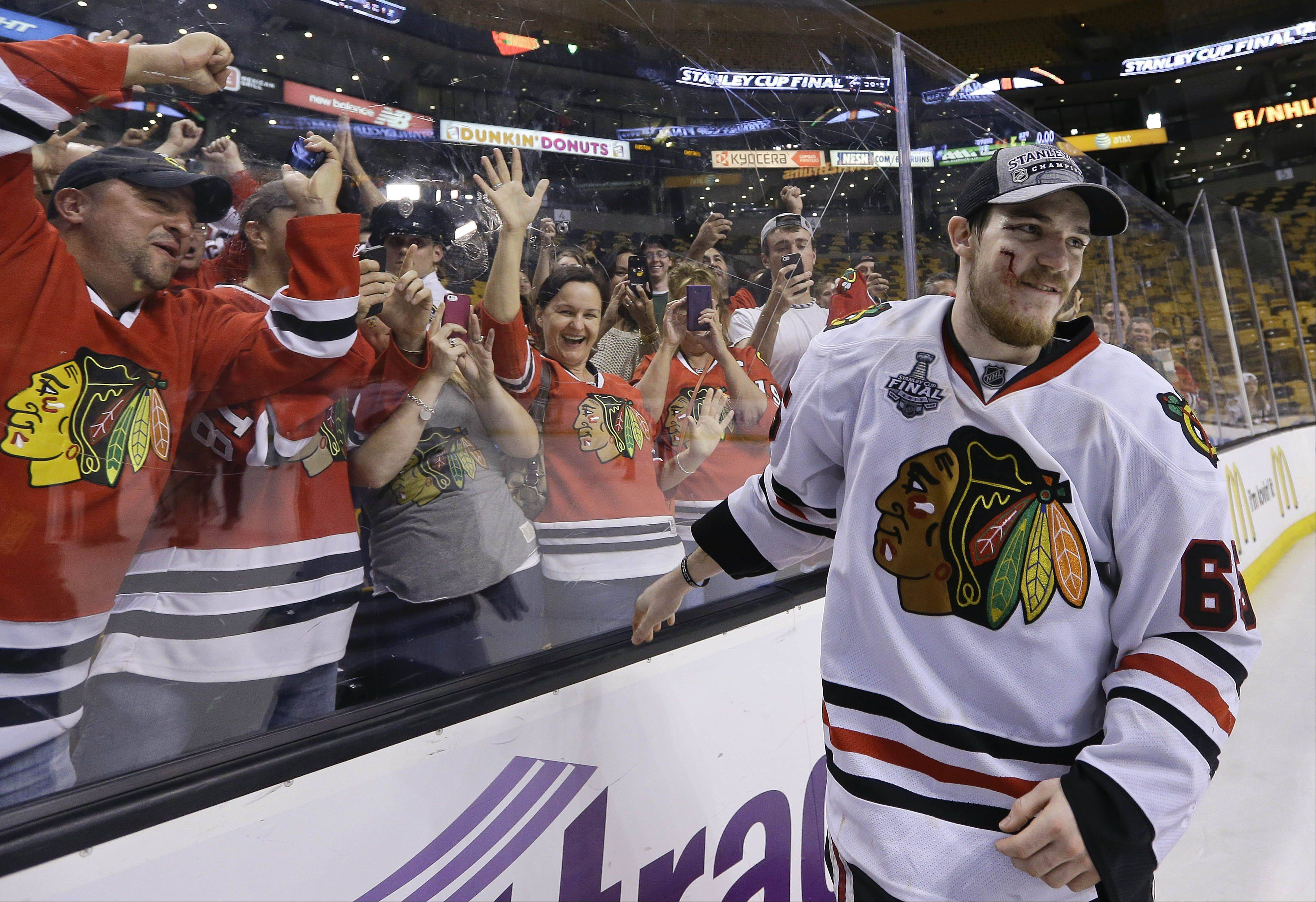 Chicago Blackhawks center Andrew Shaw skates from the glass after celebrating with fans after the Blackhawks beat the Boston Bruins in Game 6 of the NHL Stanley Cup Finals Monday.