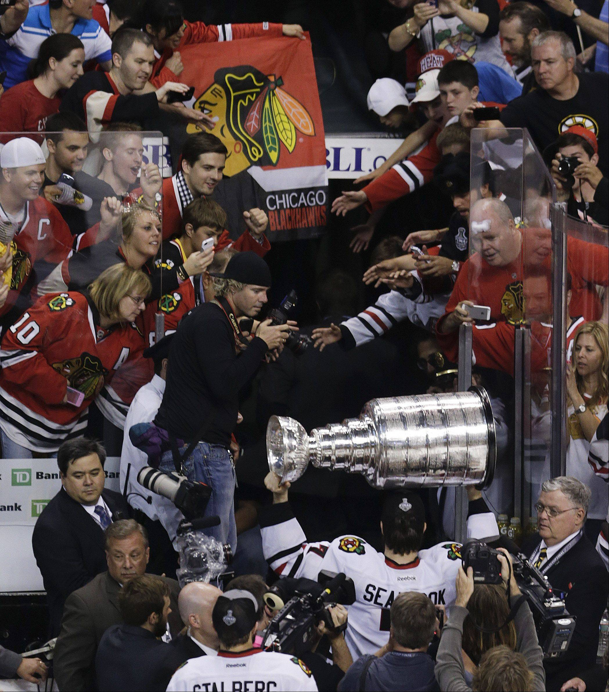 Chicago Blackhawks defenseman Brent Seabrook carries the Stanley Cup off the ice amid Blackhawks fans after the Blackhawks beat the Boston Bruins in Stanley Cup Finals Monday.