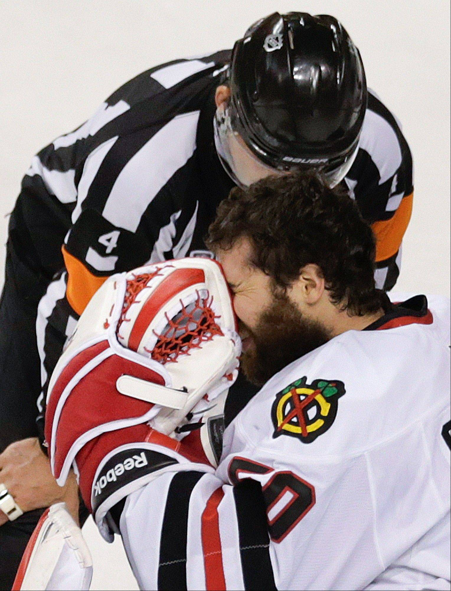 Referee Wes McCauley checks on Chicago Blackhawks goalie Corey Crawford during the first period in Game 6 of the Stanley Cup Finals against the Boston Bruins.