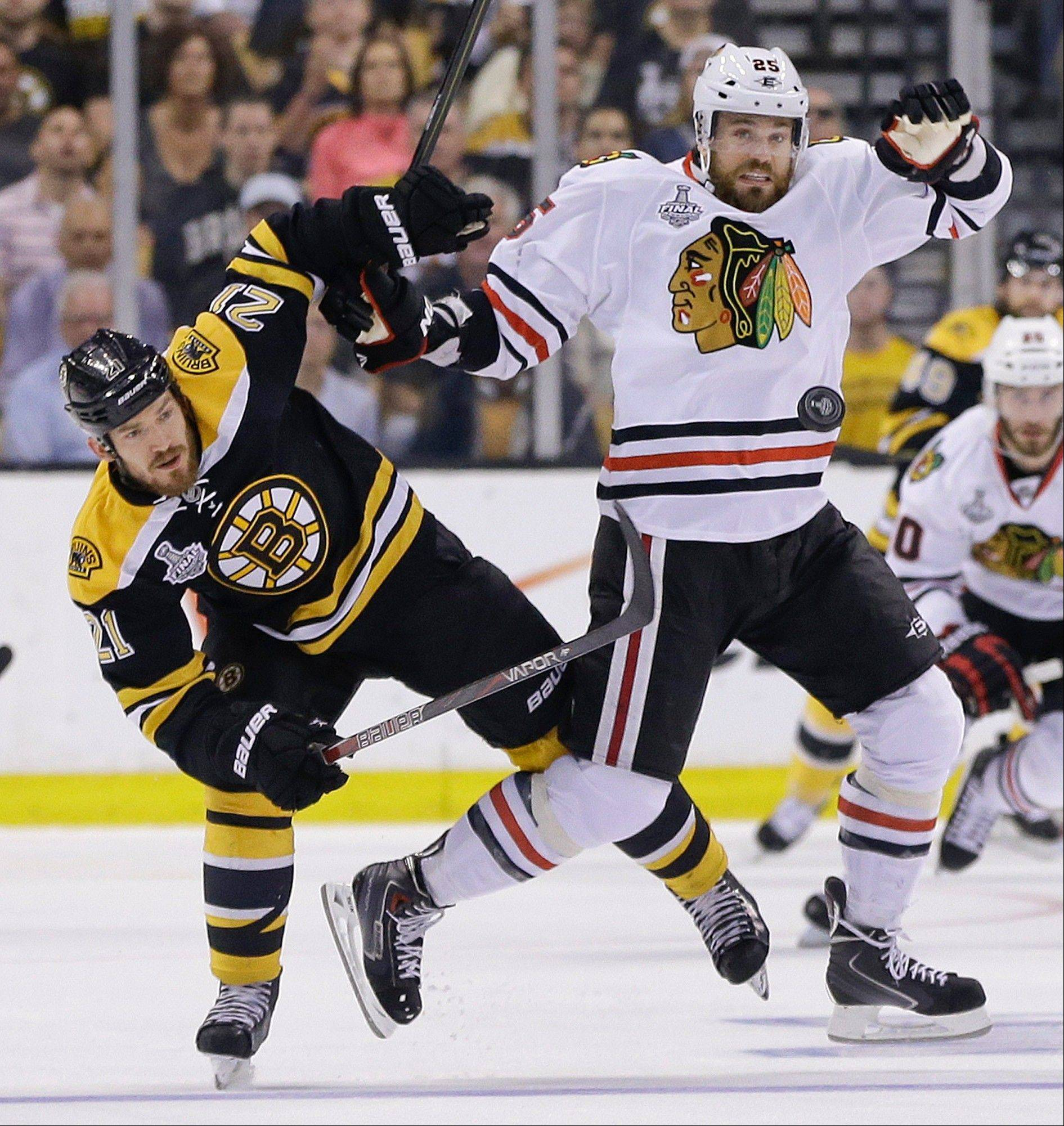 Boston Bruins defenseman Andrew Ference (21) and Chicago Blackhawks center Patrick Sharp (10) fight for position as the puck passes during the first period in Game 6 of the Stanley Cup Finals Monday in Boston.