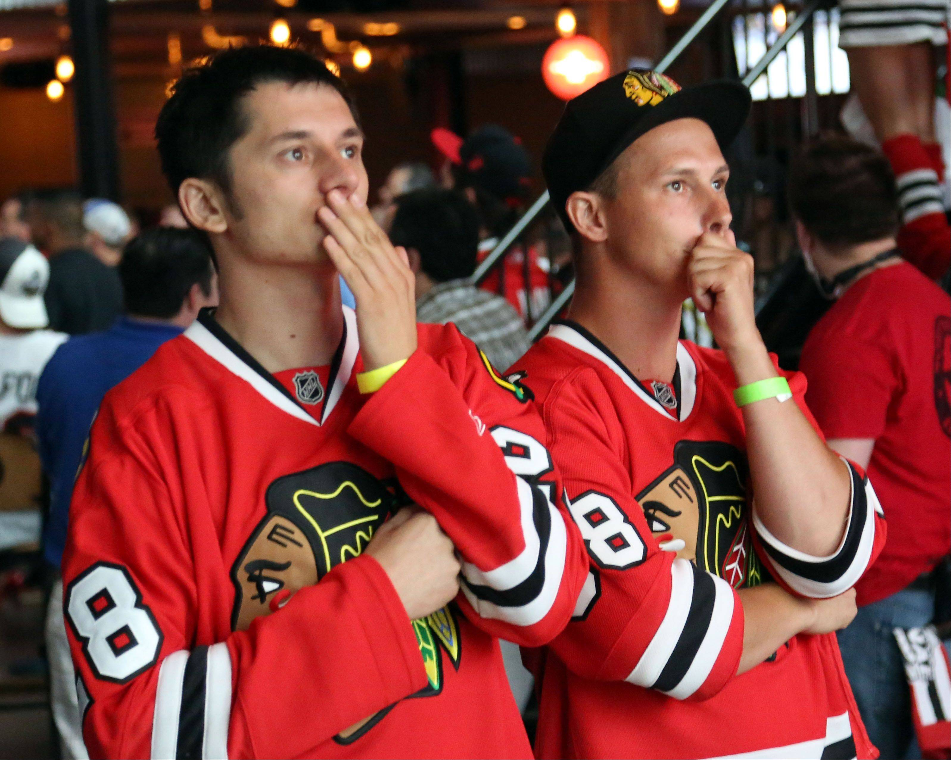 Tom Butryn and Jake Piotrowski, both of Chicago, look worried as the watch Game 6 of the Stanley Cup Finals at Toby Keith's I Love This Bar in Rosemont Monday night.