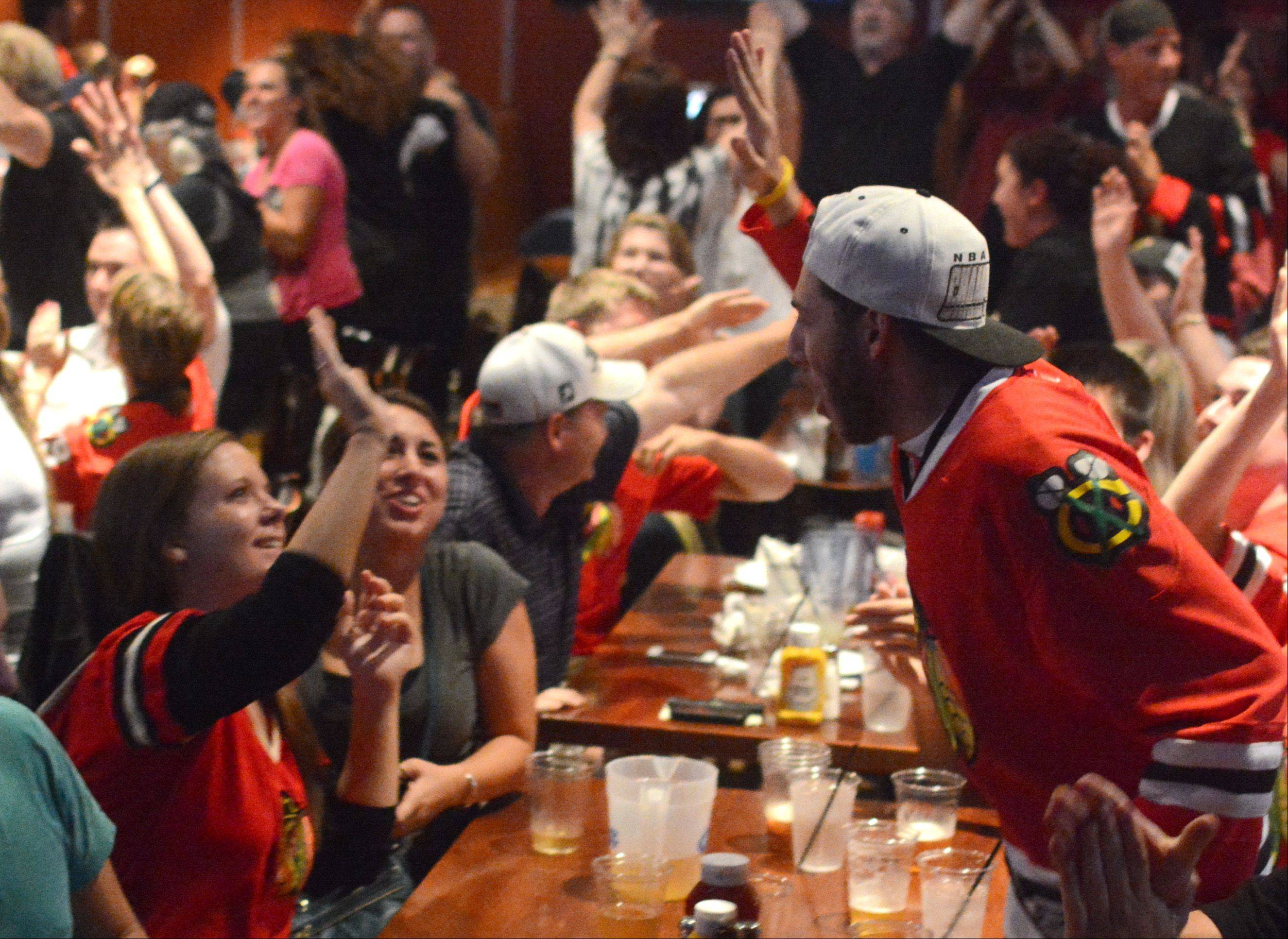 Nate Richards, right, of Buffalo Grove, high fives Jorie O'Neill of Wheeling, as the Blackhawks tie up Game 6 of the Stanley Cup Final at the Cubby Bear North in Lincolnshire Monday.