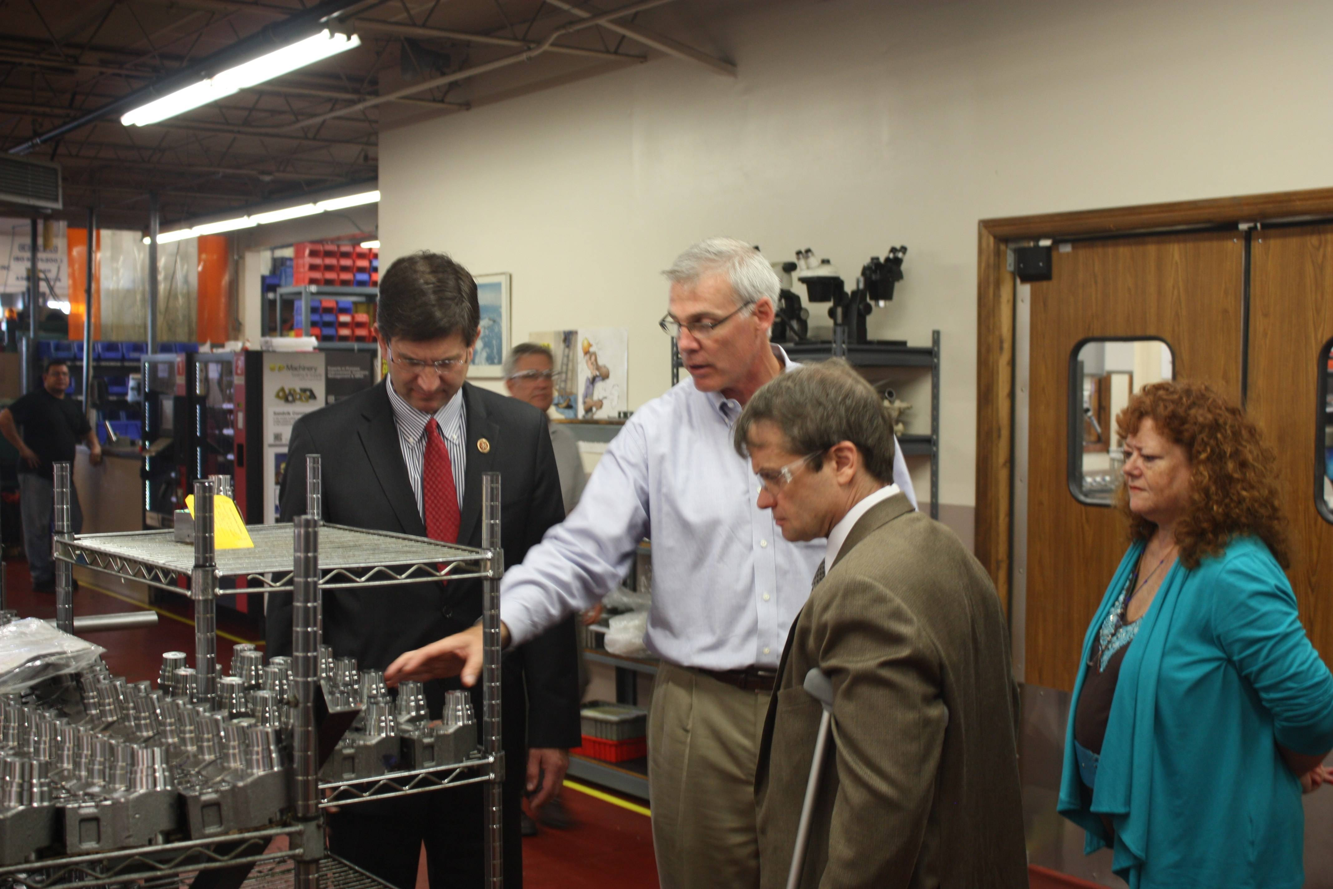 Chucking Machine Products President Tim Merrigan discusses manufacturing issues with Congressmen Brad Schneider (L) and Mike Quigley as Illinois Alliance of Manufacturing President Pam McDonough looks on.