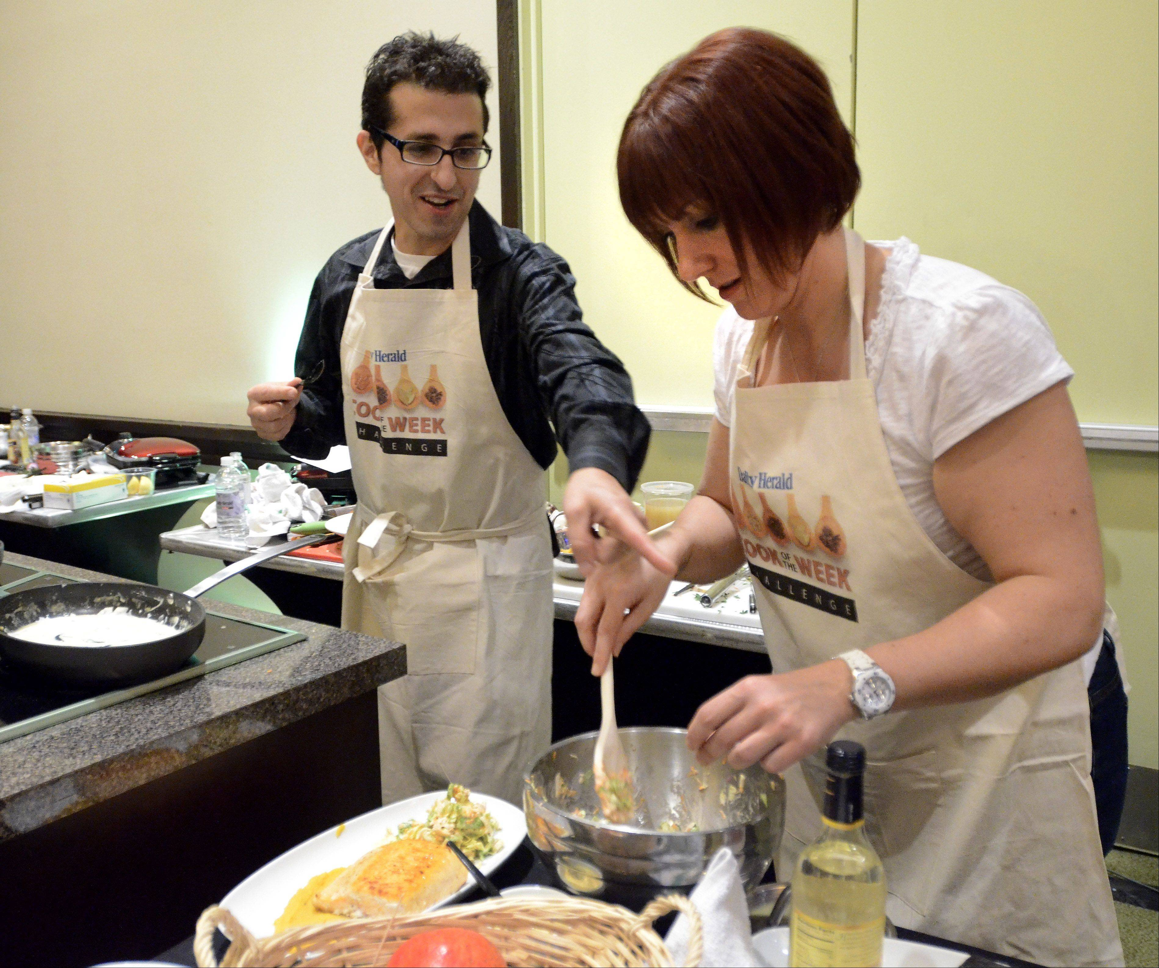 Michael Pennisi gets help from his sister, Mary Samycia, as he prepares his dish during the Cook of the Week Challenge cook-off. A physics teacher from Carpentersville, Pennisi bested 15 other home cooks last year for the title of Daily Herald Cook of the Year.