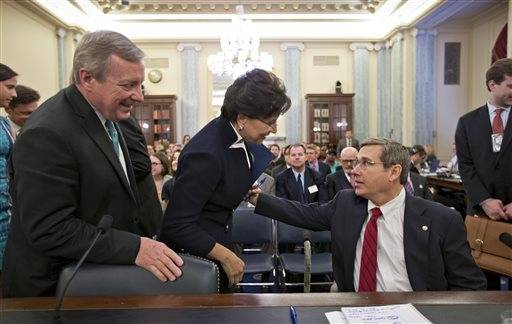 This May 23, 2013 file photo shows Sen. Mark Kirk being greeted Chicago billionaire business executive Penny Pritzker, President Obama's pick for Commerce Secretary, and Senate Majority Whip Richard Durbin on Capitol Hill in Washington as she arrives for her nomination hearing before the Senate Commerce Committee.