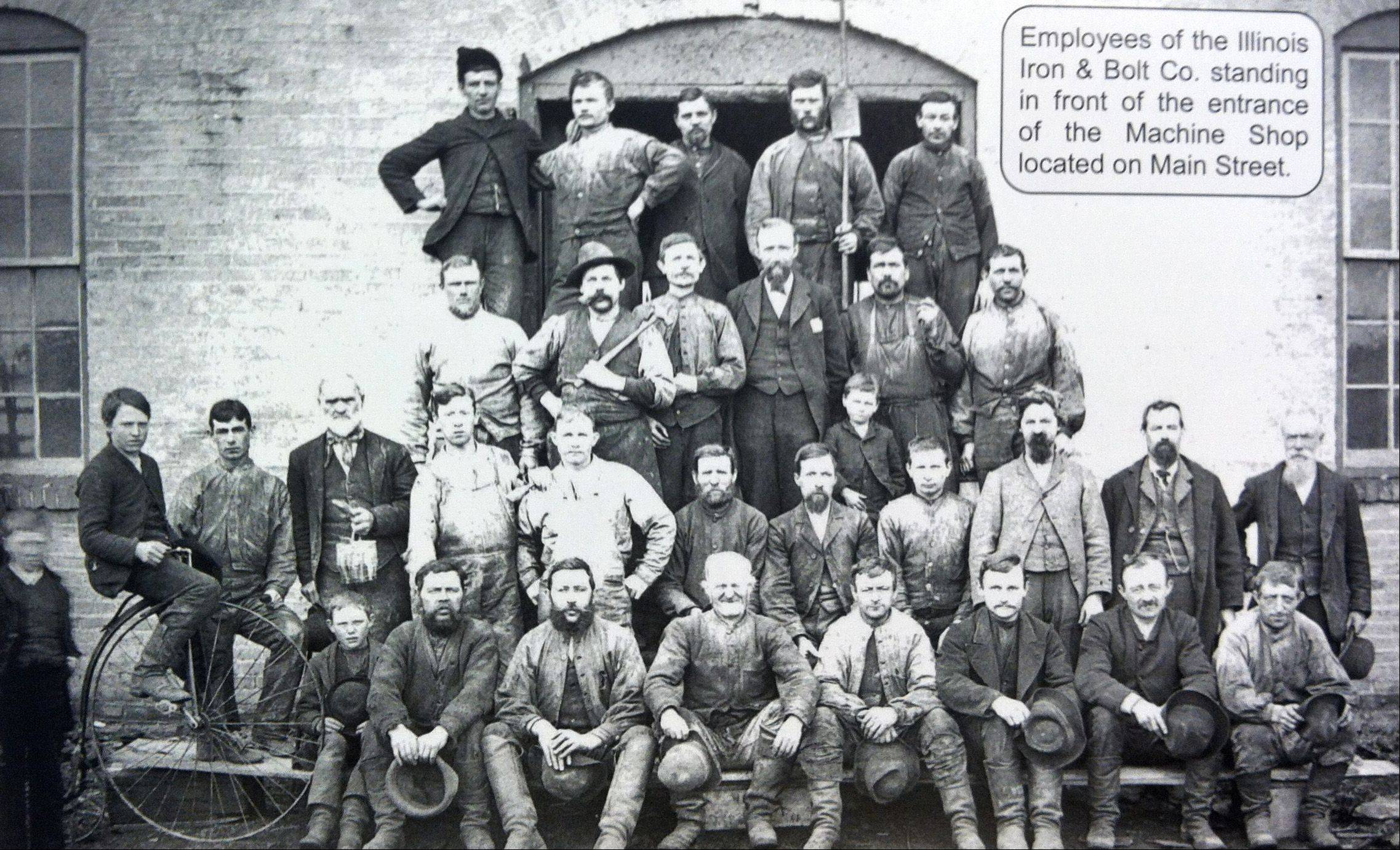 In this undated photograph, workers from the Illinois Iron & Bolt Company stand in front of the company's machine shop on Main Street. The company's workweek was 10 hours a day and six days a week.