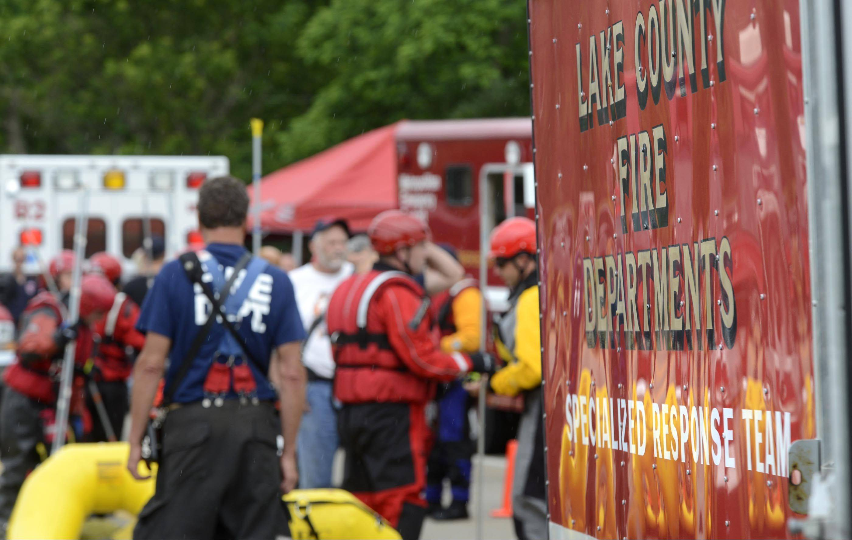 Multiple rescue crews gather on the Kelsey Road bridge in Lake Barrington to look for a reported person and dog in a fast-moving, flooded creek in the Grassy Lake Forest Preserve after noon Wednesday.