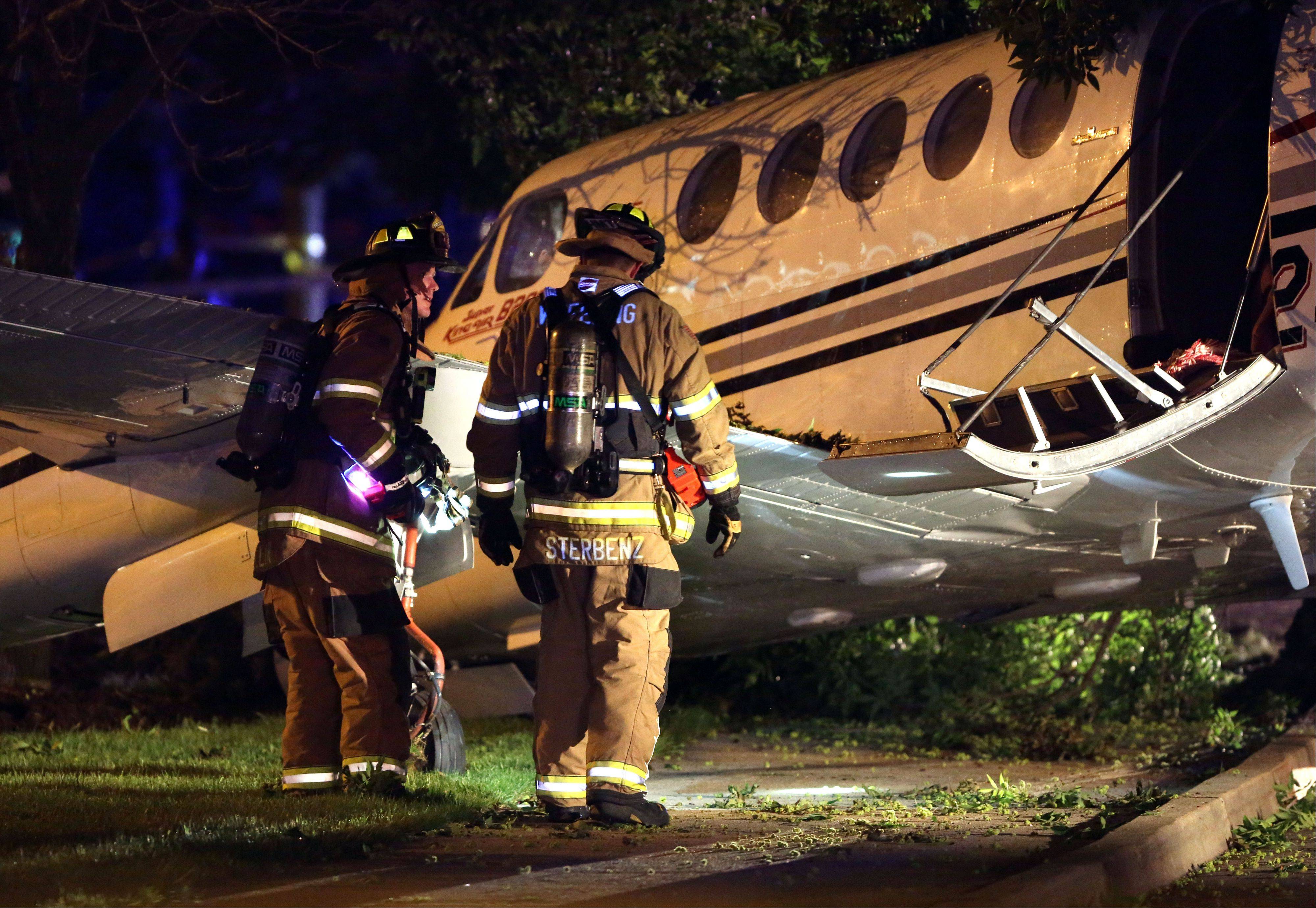 Firefighters investigate a plane that crashed on Wolf Road in Wheeling near the Foxboro Apartments Tuesday night.