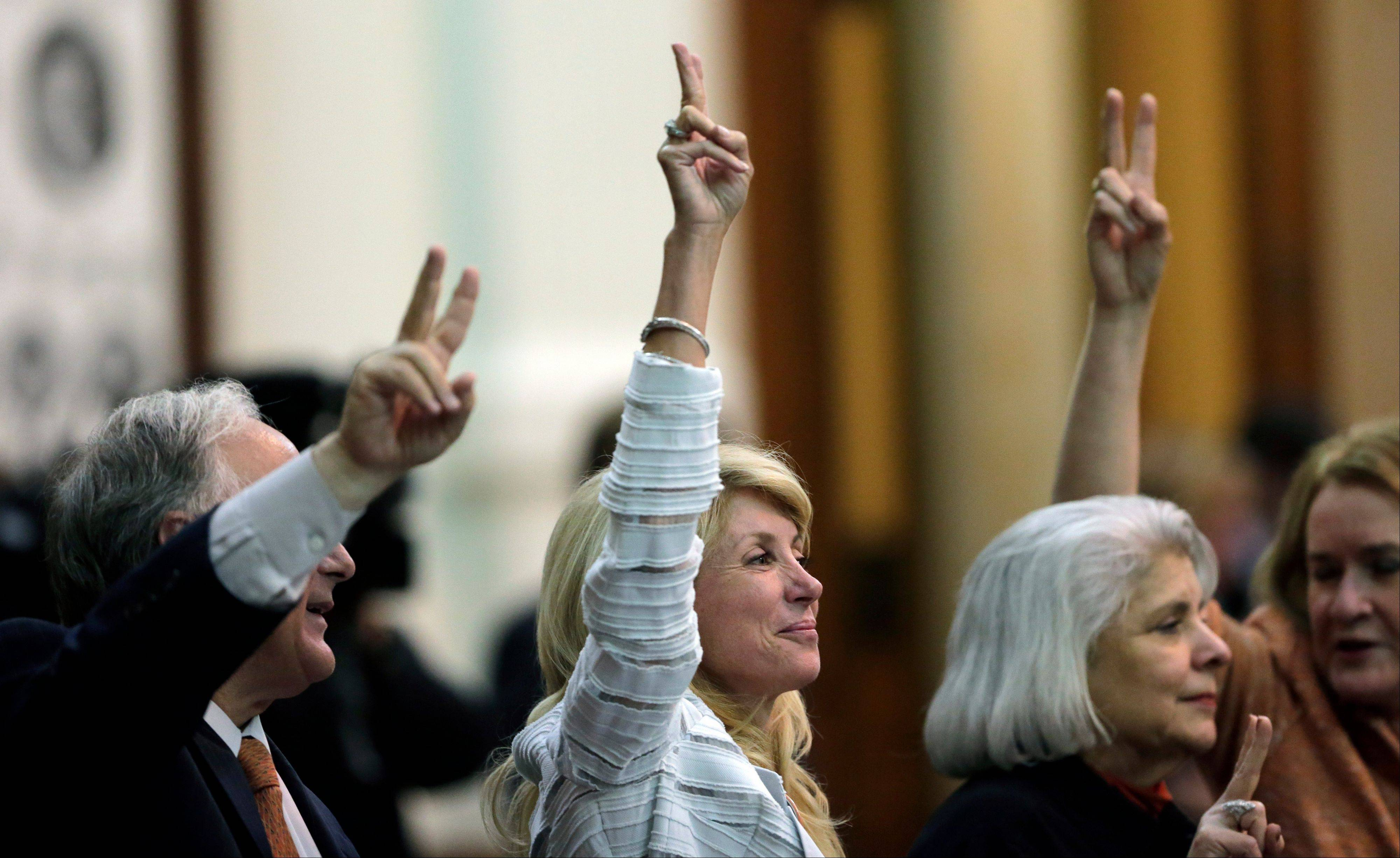 "Sen. Wendy Davis, a Democrat from Fort Worth, center, holds up two fingers late Tuesday to signal a ""No"" vote as the session where they tried to filibuster an abortion bill draws to a close."