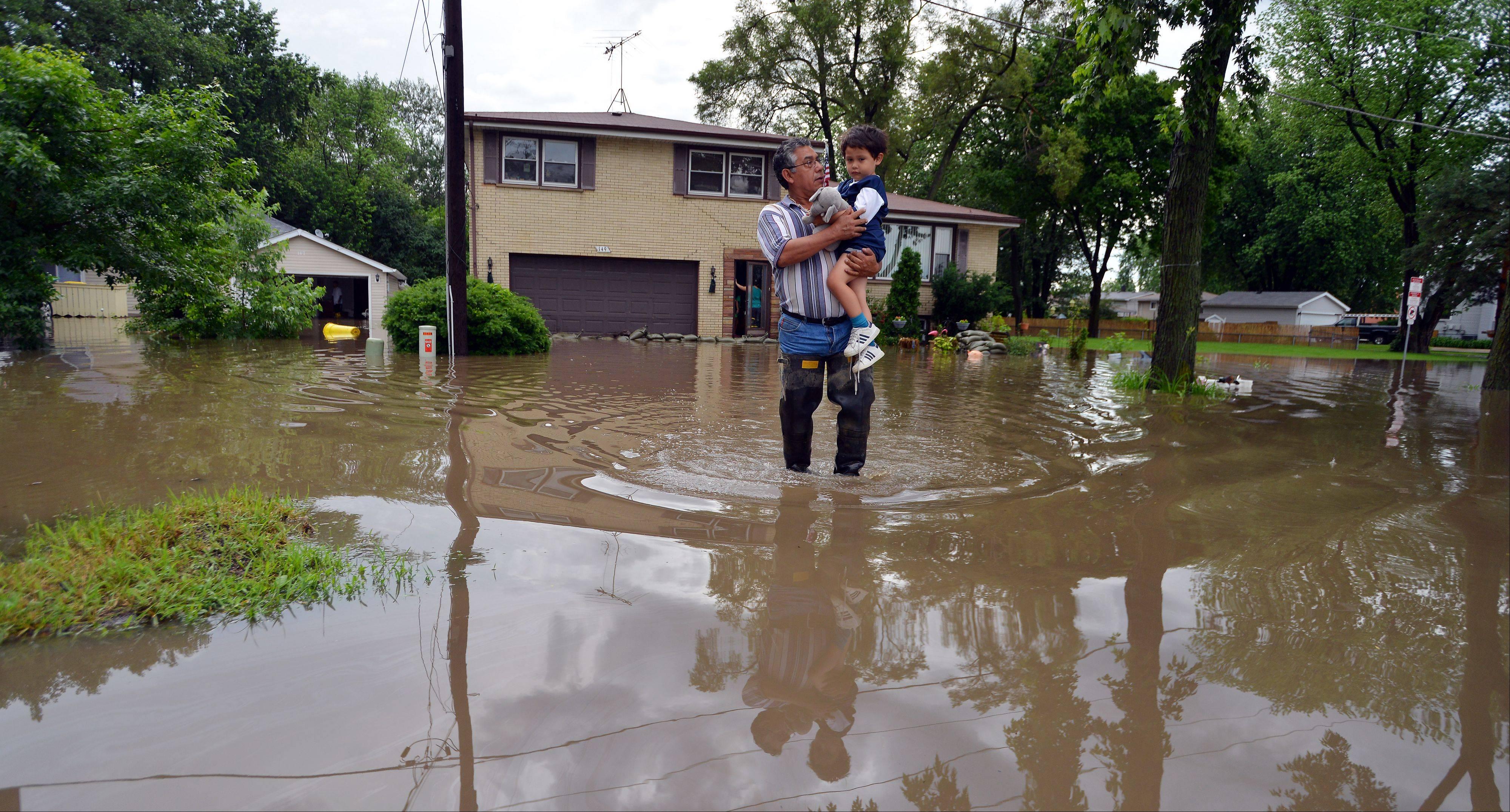 Juan Corona carries his grandson Felix Hernandez, four, from his flooded house which belongs to his daughter Alex Hernandez in Wheeling after storms dumped over five inches of water in a matter of hours. The house has over five feet of water in the basement and was still rising.