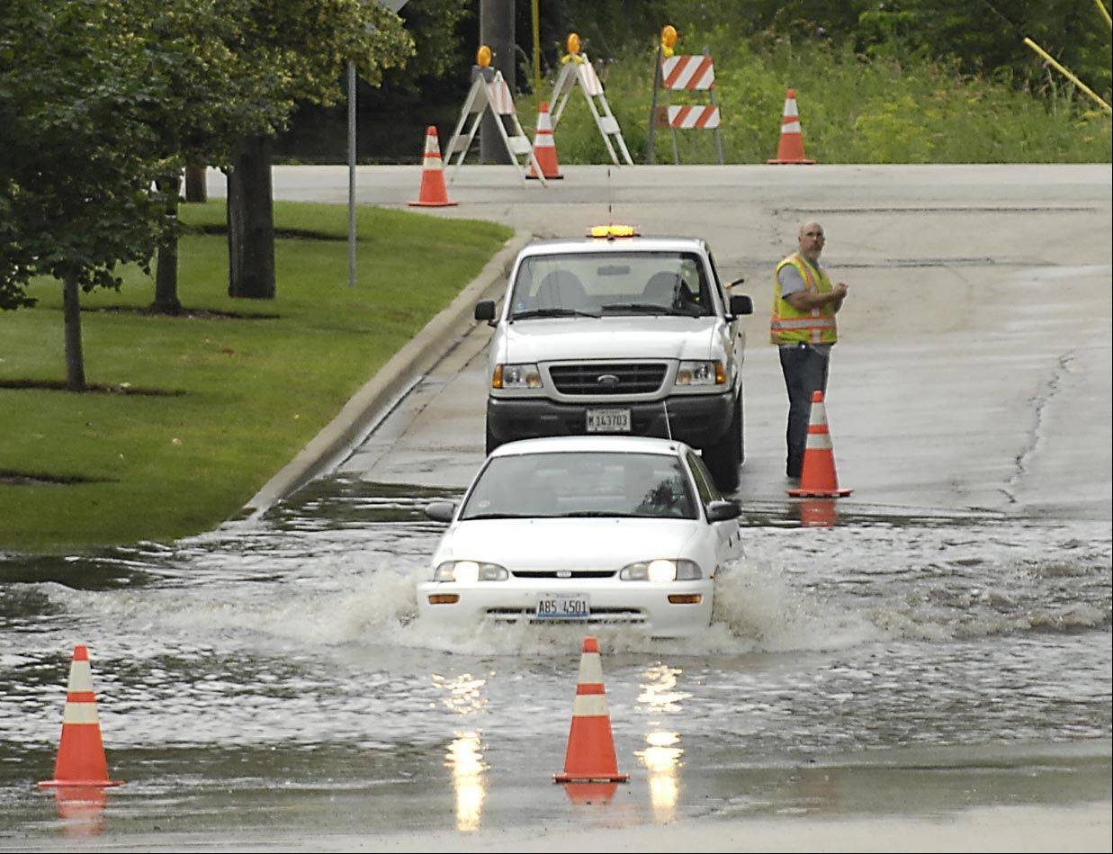 A small car pushes it's way through a flooded Knack Road, near Route 176 in Crystal Lake Wednesday morning. Continuous overnight storms flooded many streets in McHenry County.
