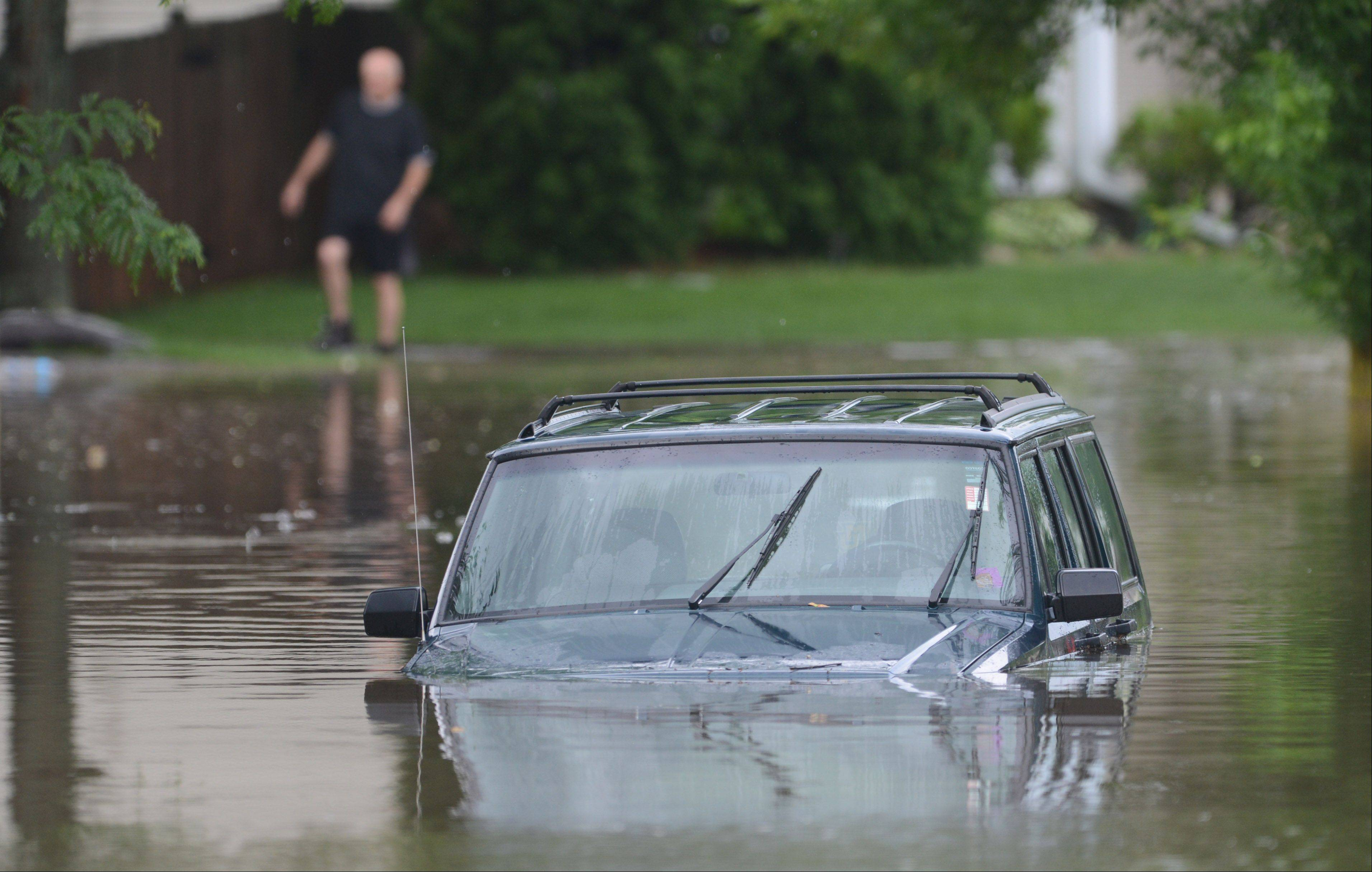 A car is submerged under water along Bristol Trail Road in Lake Zurich as heavy rains hit the area Wednesday morning.