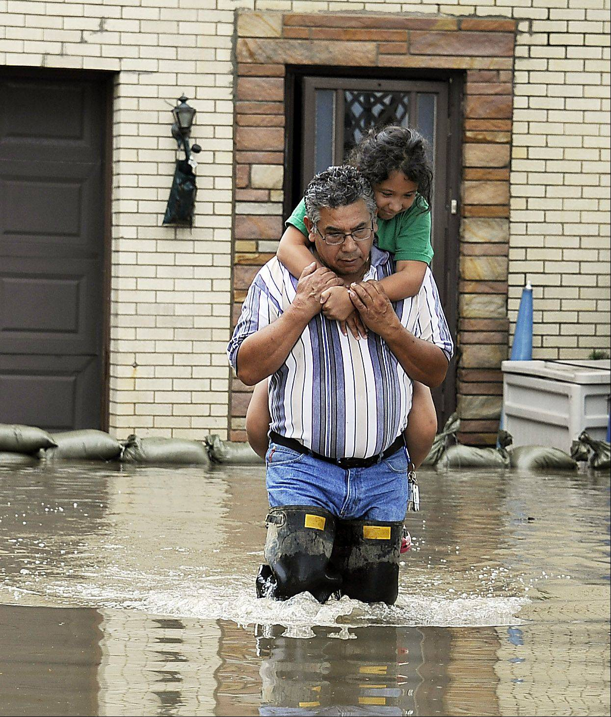 Juan Corona carries his granddaughter Delanee Hernandez, 9, on his back from her flooded house in Wheeling after storms dumped over five inches of water on the area.