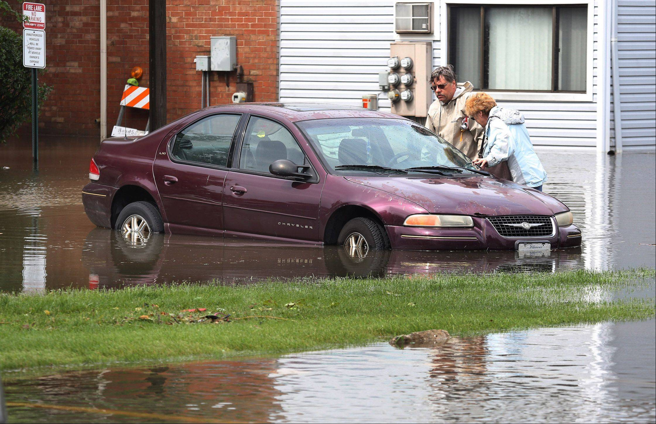 Kurt and Cheryl Prell inspect the condition of their car after flooding at the Runaway Bay Apartments in Palatine on Wednesday.