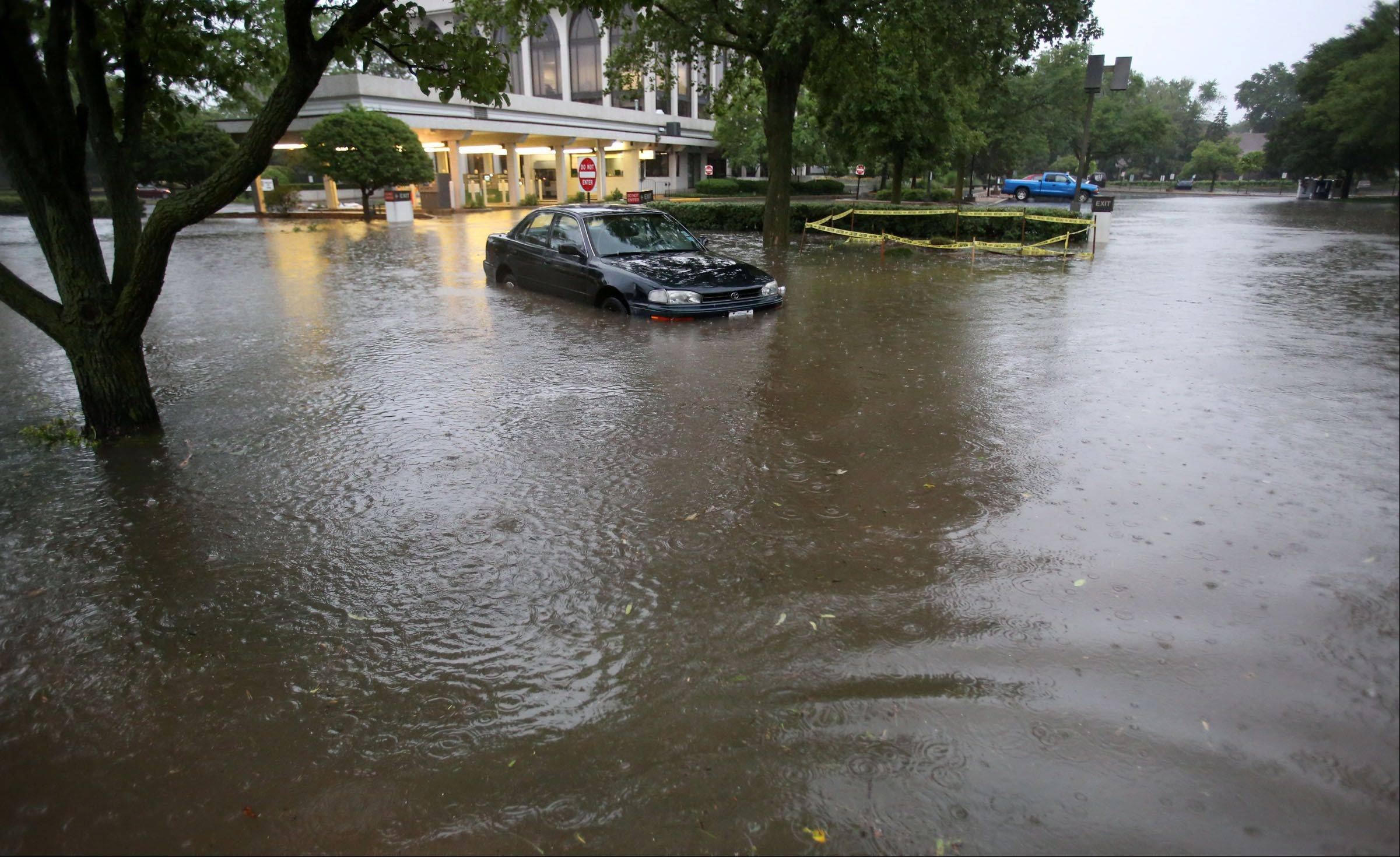 An abandoned car sits on flooded Henley Street in front of Glenview State Bank at Waukegan Road in Glenview on Wednesday.