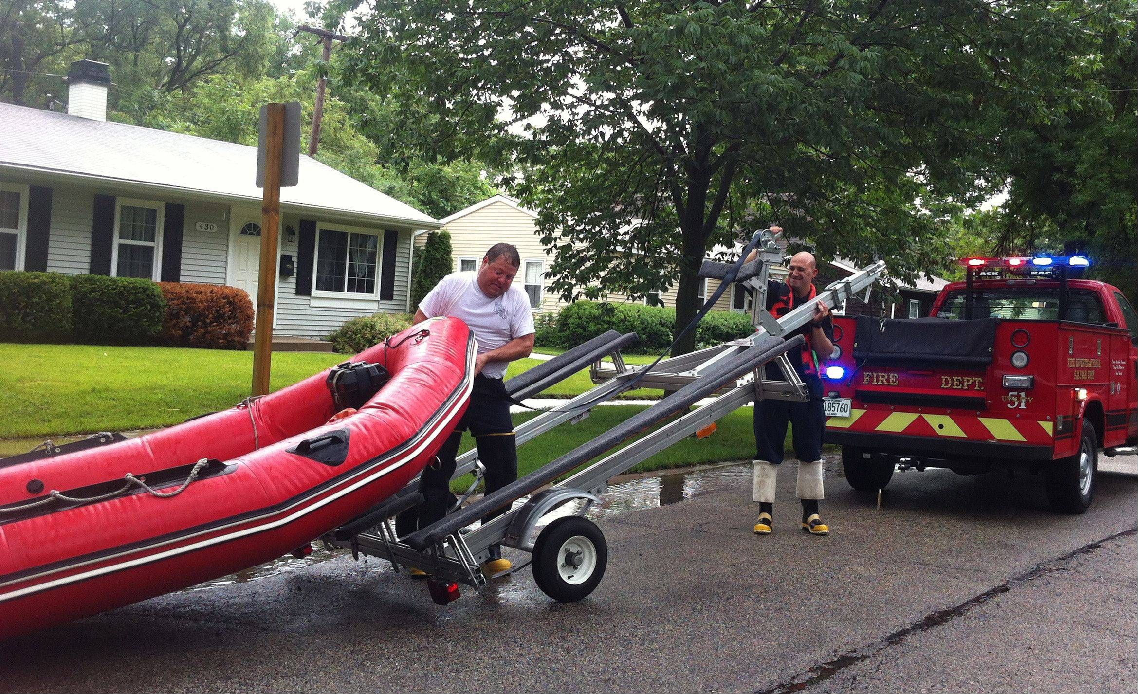 Buffalo Grove Fire Department personnel load a rescue boat back onto a trailer Wednesday after helping to evacuate some nearby residents as floodwaters rose in their homes.