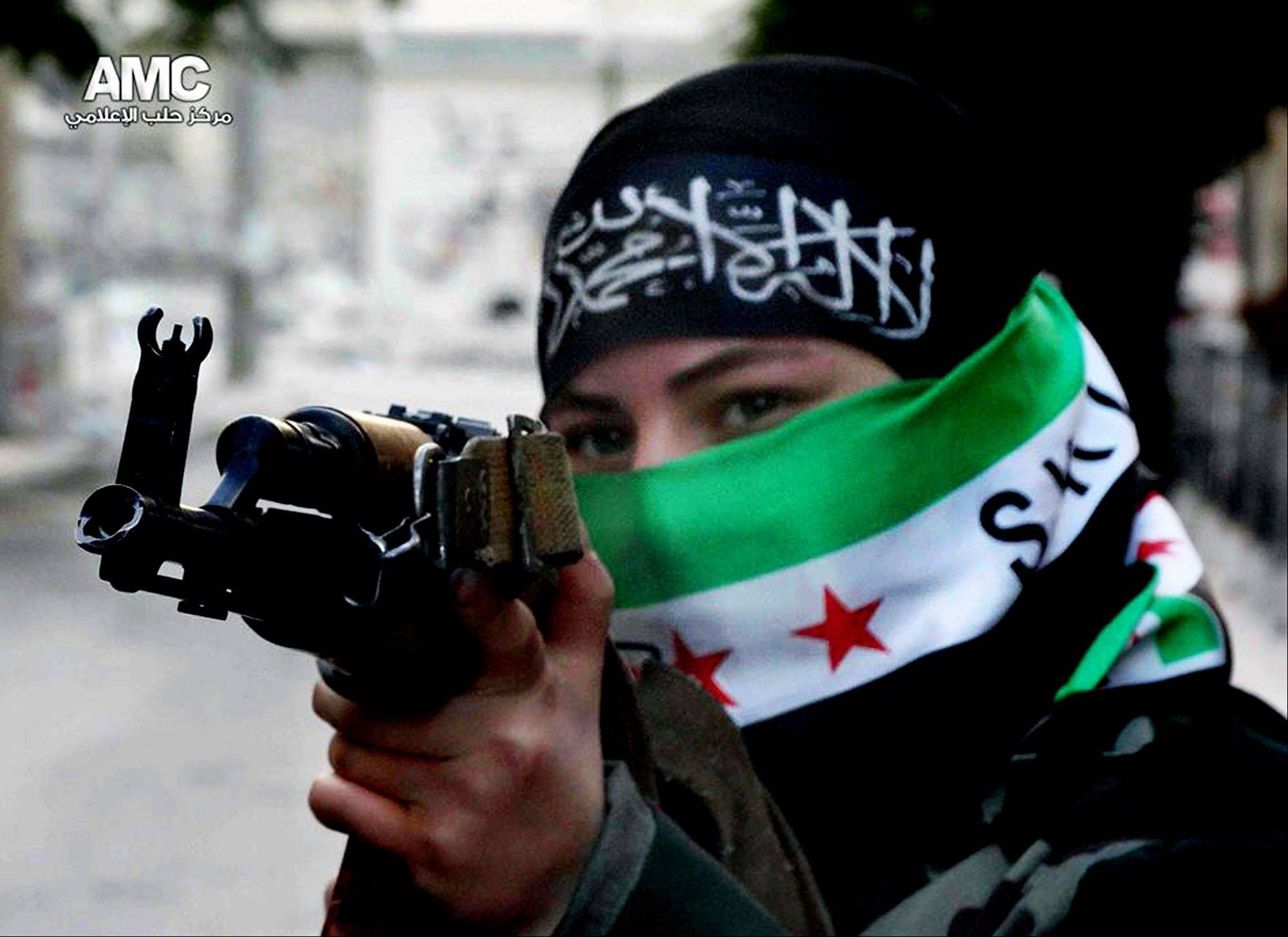This Tuesday, June 25, 2013 citizen journalism image provided by Aleppo Media Center AMC which has been authenticated based on its contents and other AP reporting, shows a female Free Syrian Army fighter aiming her weapon, in Aleppo, Syria.