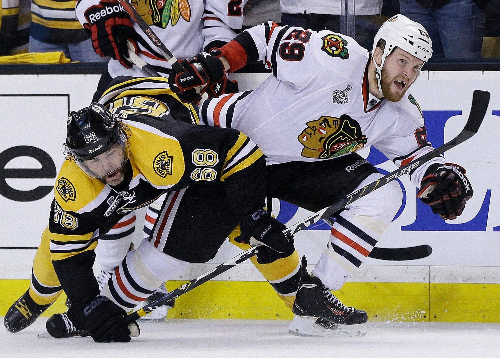 Boston Bruins right wing Jaromir Jagr (68), of the Czech Republic, ties up Chicago Blackhawks left wing Bryan Bickell (29) during the third period in Game 3 of the NHL hockey Stanley Cup Finals in Boston, Monday, June 17, 2013. The Bruins won 2-0.