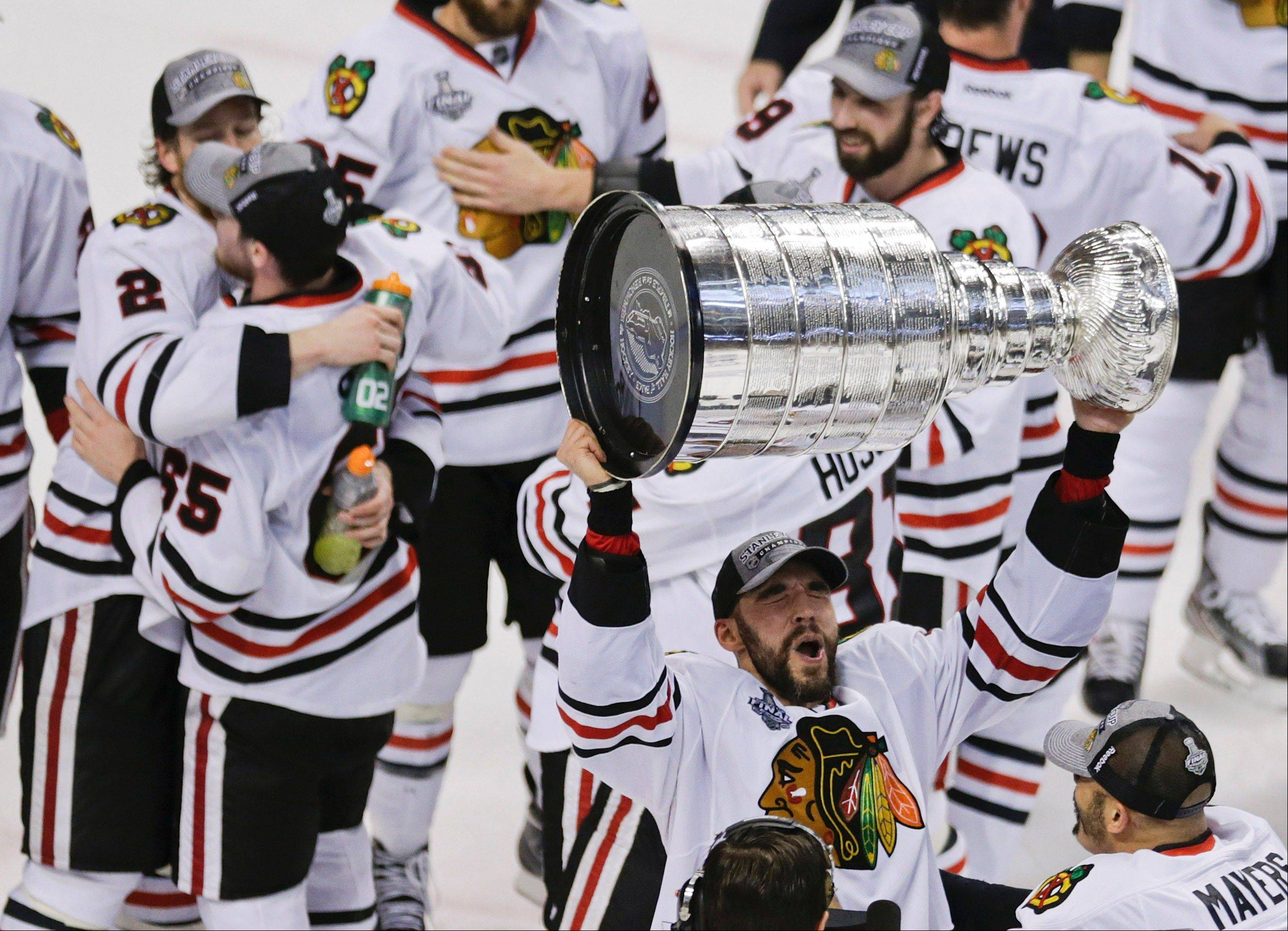 Michal Rozsival hoists the Stanley Cup after the Blackhawks defeated the Boston Bruins 3-2 in Game 6 of the Stanley Cup Final on Monday night.