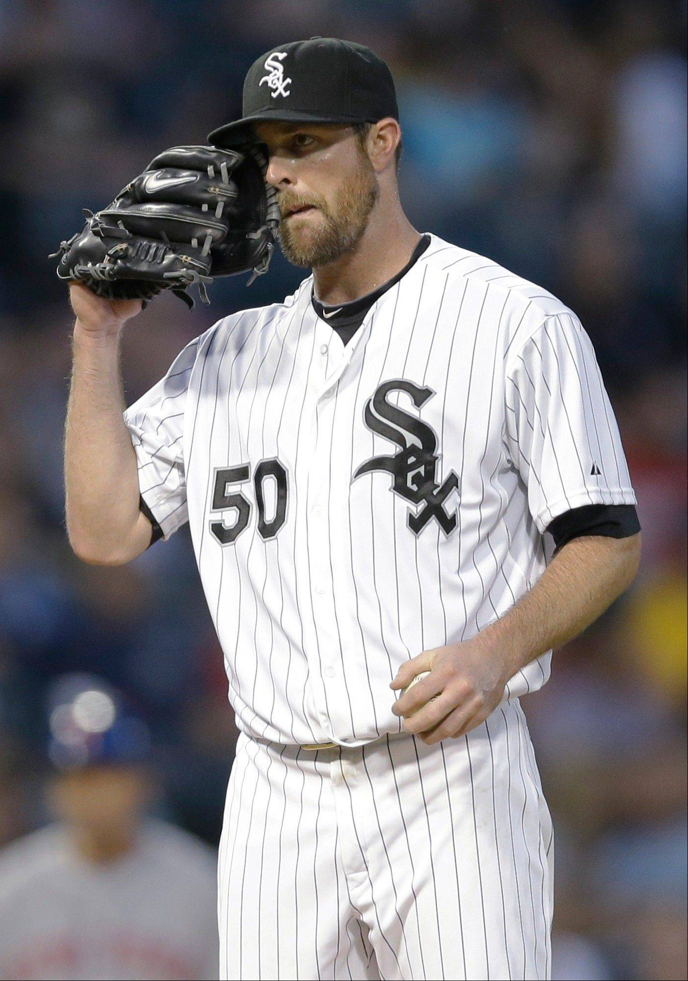 White Sox starter John Danks wipes his face after New York Mets' Eric Young Jr. hit an RBI single during the fifth inning of an interleague baseball game Wednesday, June 26, 2013, in Chicago.