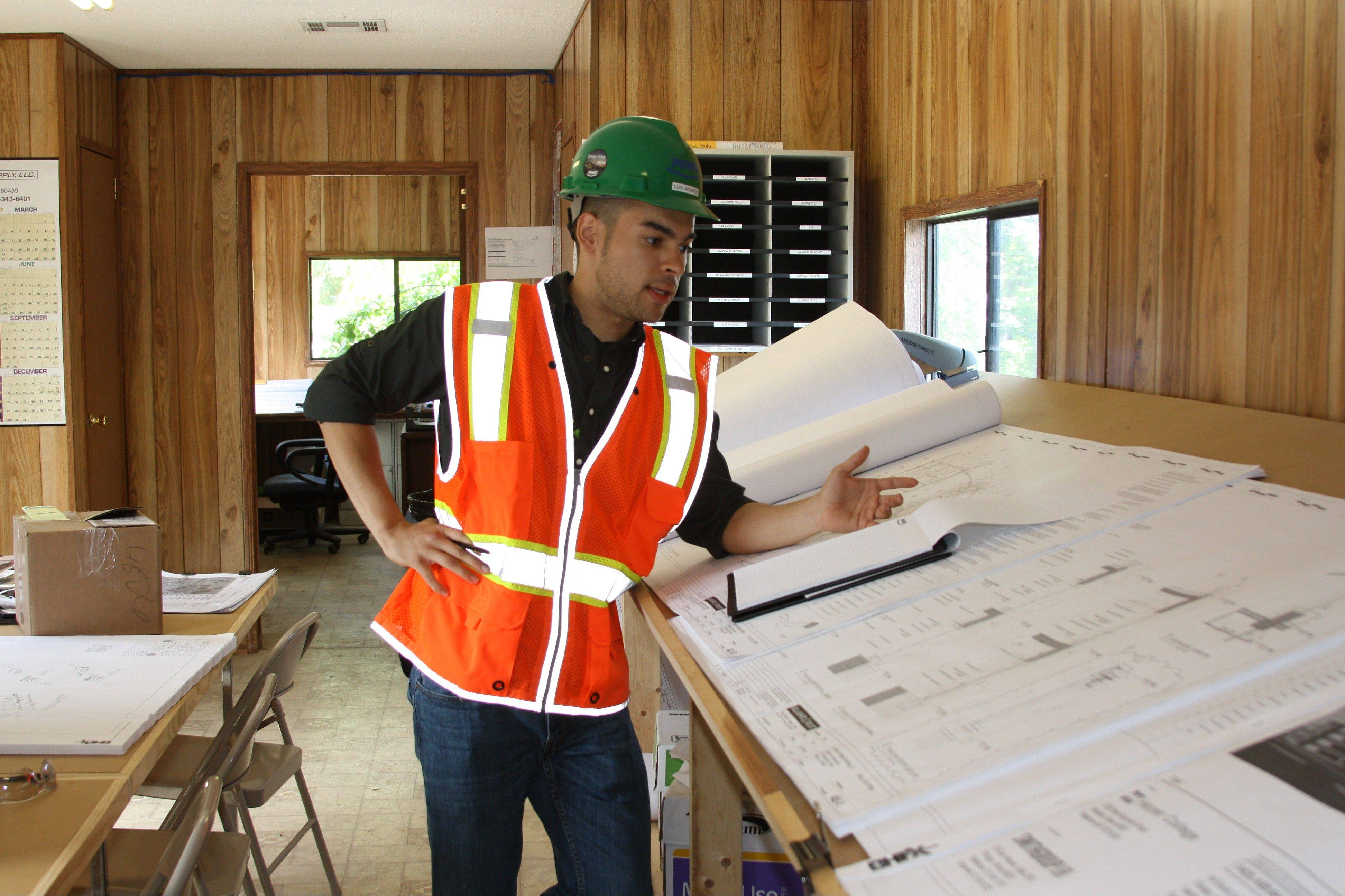 Harper College student Luis Monroy reviews architectural drawings as part of his internship with Power Construction, the company chosen to lead the college's campus reconstruction.