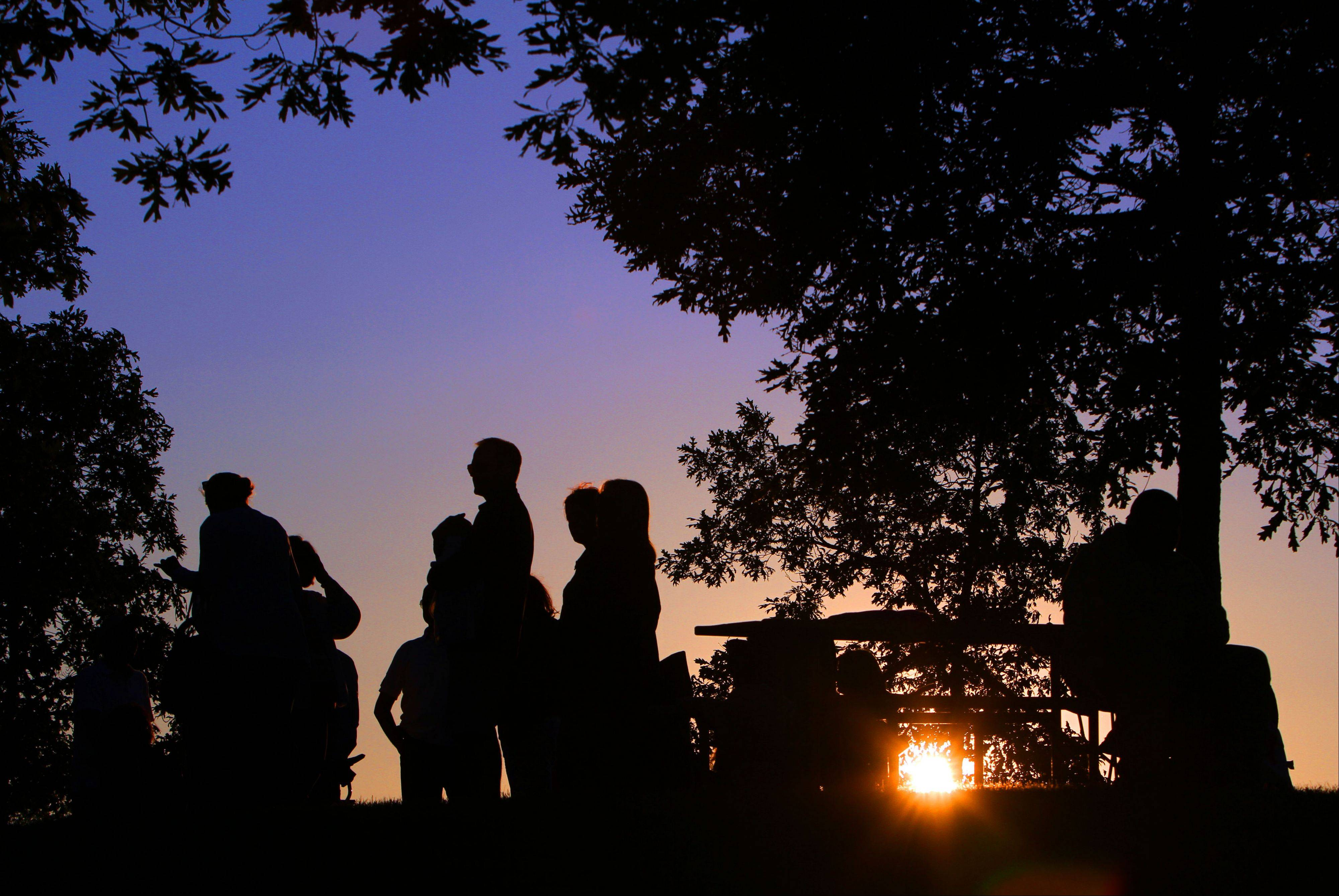 People picnic as the sun sets during the first night of Events in the Plaza outdoor summer concert series Tuesday night at Independence Grove Forest Preserve in Libertyville.