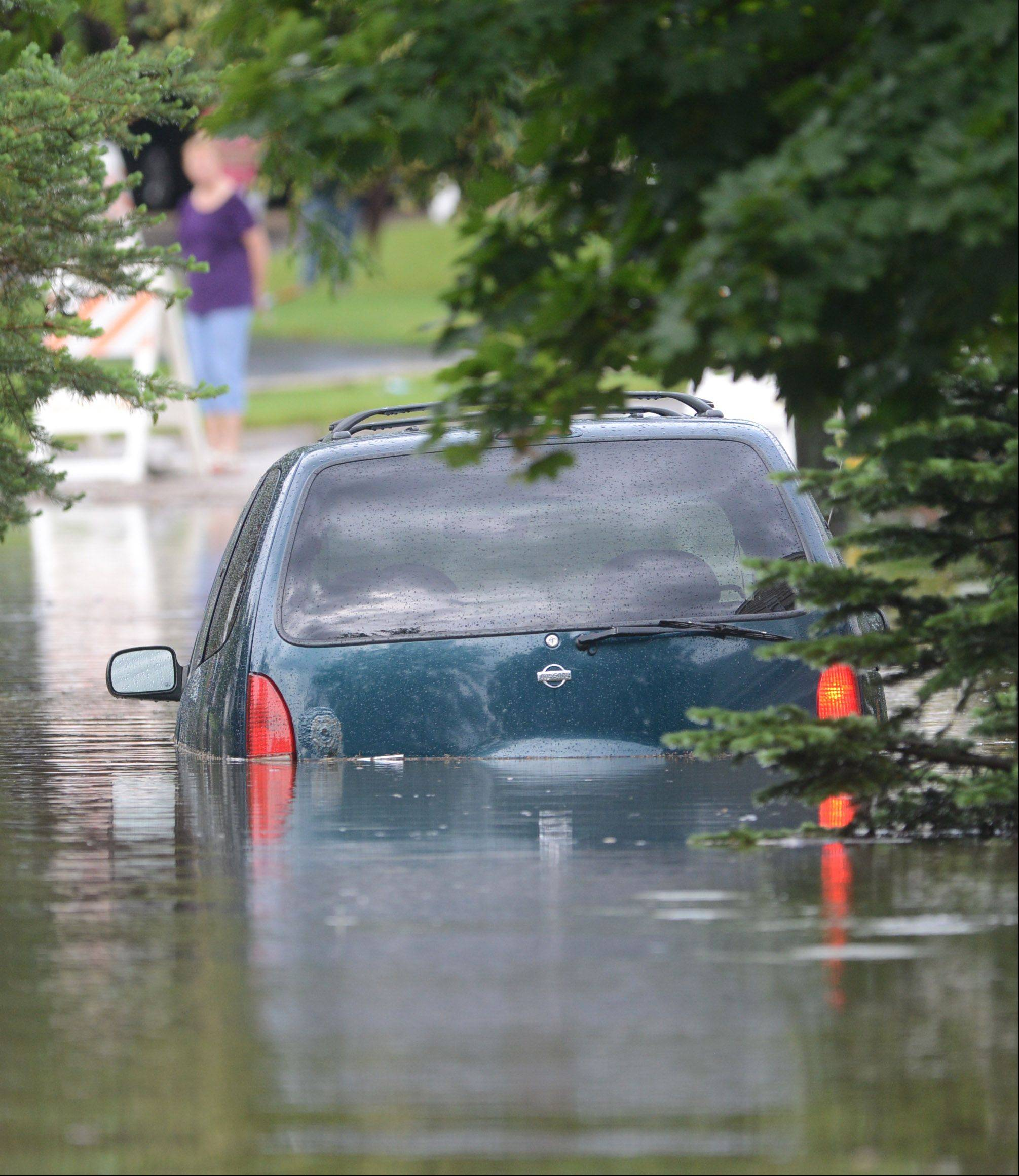 Paul Valade/pvalade@dailyherald.com A vehicle is half under water along Bristol Trail Drive in Lake Zurich Wednesday following heavy rains.
