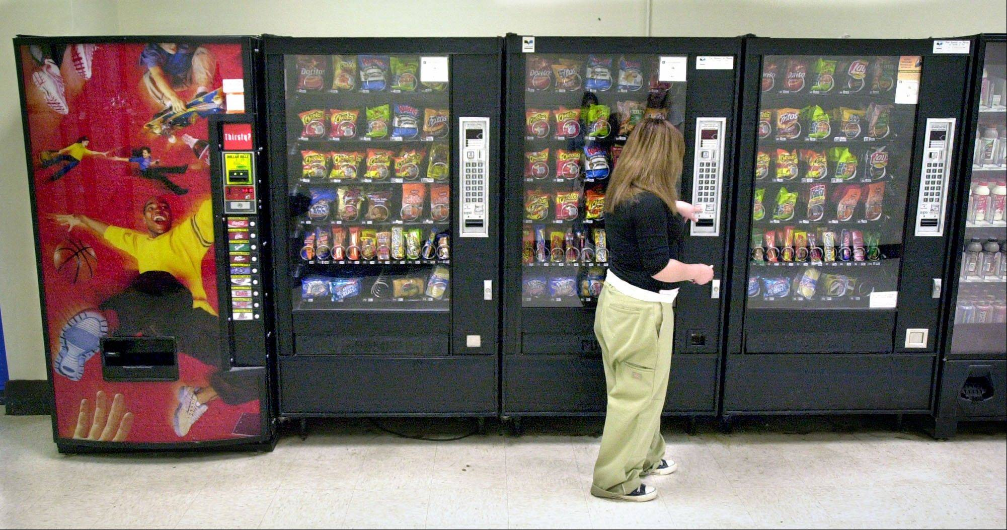 A student purchases a brown sugar Pop-Tart from a vending machine in the hallway outside the school cafeteria, in Wichita, Kan. High-calorie sports drinks and candy bars will be removed from school vending machines and cafeteria lines as soon as next year, replaced with diet drinks, granola bars and other healthier items the Agriculture Department said Thursday.