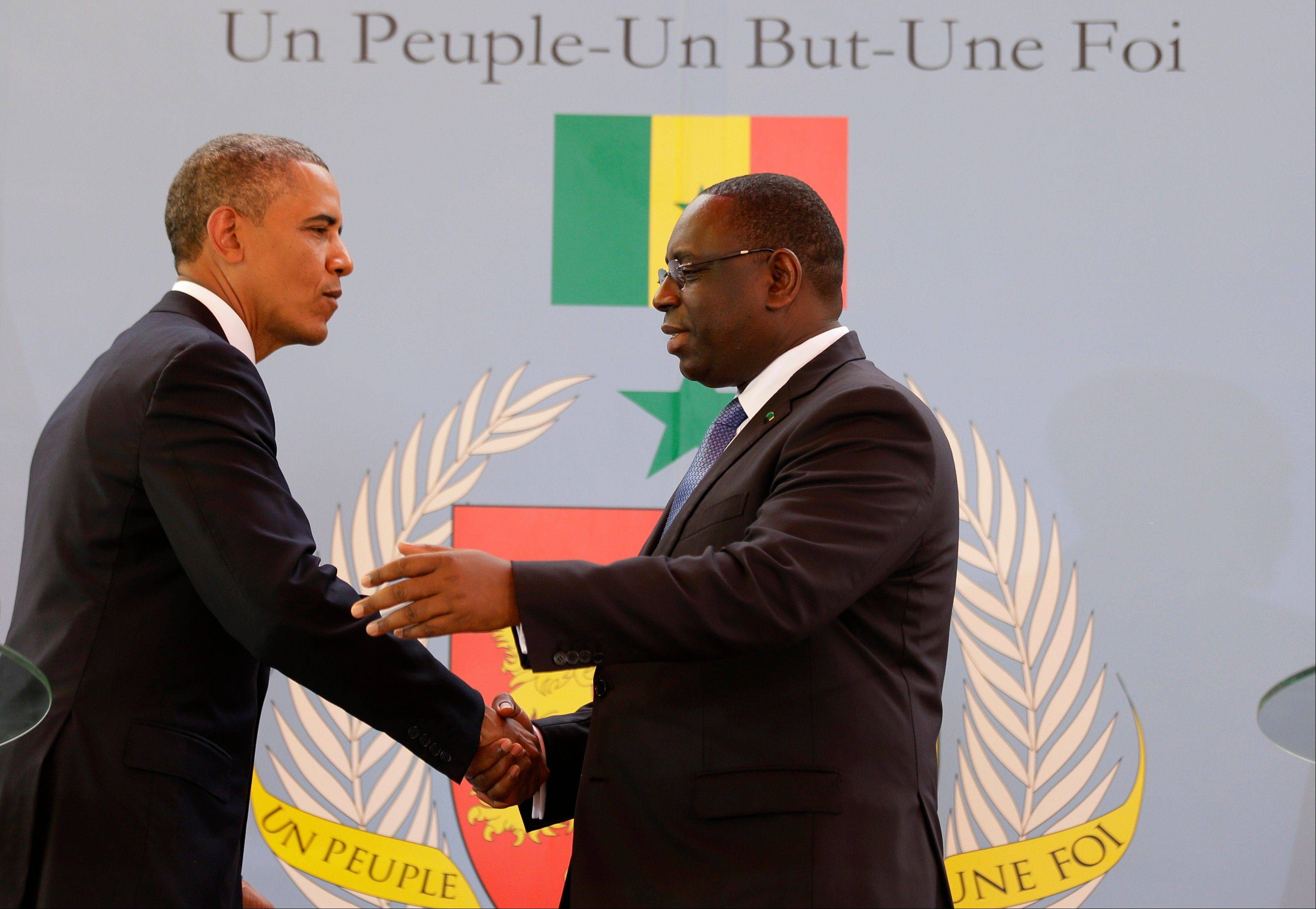 U.S. President Barack Obama, left, shakes hands with Senegalese President Macky Sall after a joint press conference at the presidential palace in Dakar, Senegal, Thursday, June 27, 2013. Senegal�s national slogan, printed on the wall behind them, reads �One People, One Goal, One Faith.�