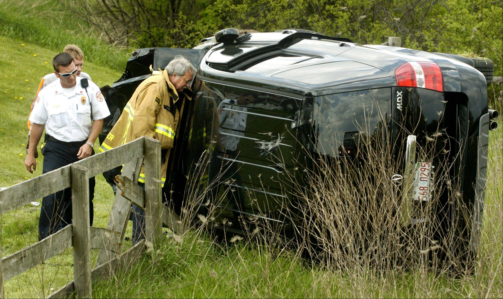 Greater Round Lake Fire Protection District's John Whitten, left, now on paid leave pending a disciplinary hearing, was a captain when he helped at this one-car rollover crash in Round Lake Park in 2005.