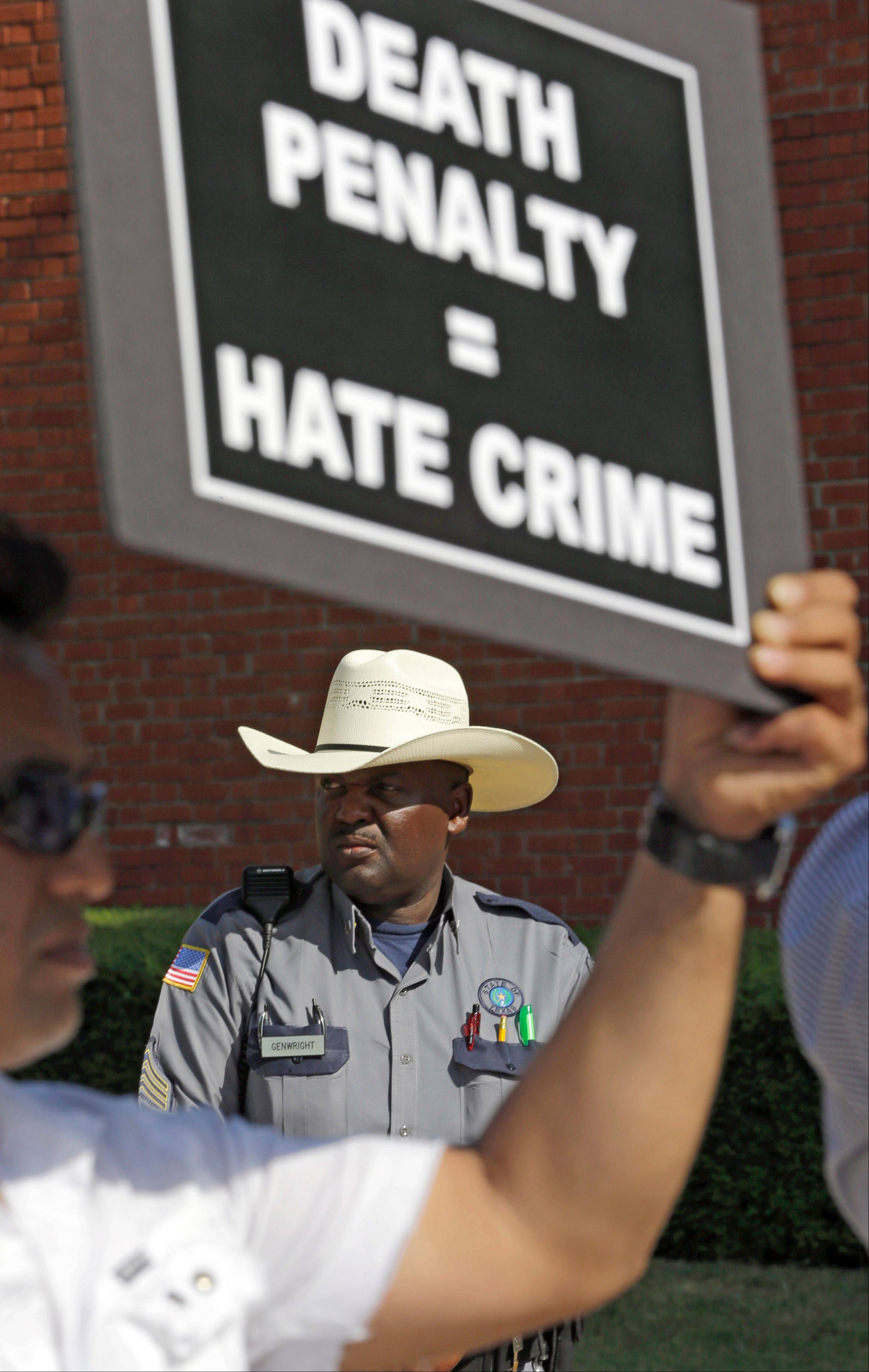 A corrections officer watches as demonstrators protest the execution of Kimberly McCarthy on Wednesday, June 26, 2013 outside the Texas Department of Criminal Justice Huntsville Unit.