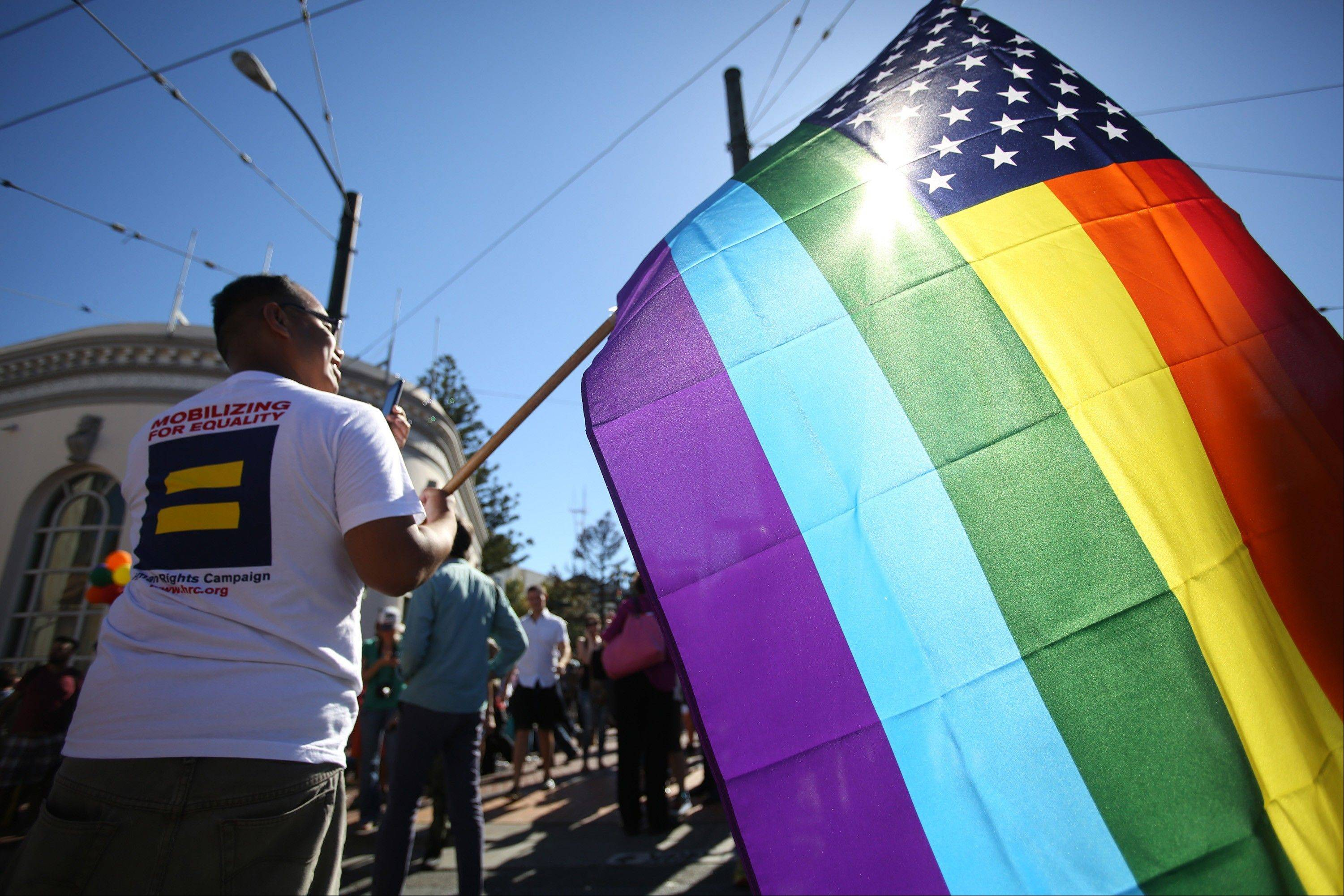 Larry Pascua carries a rainbow flag at a celebration for the U. S. Supreme Court's rulings on Prop. 8 and the Defense of Marriage Act in the Castro District in San Francisco, on Wednesday, June 26, 2013.