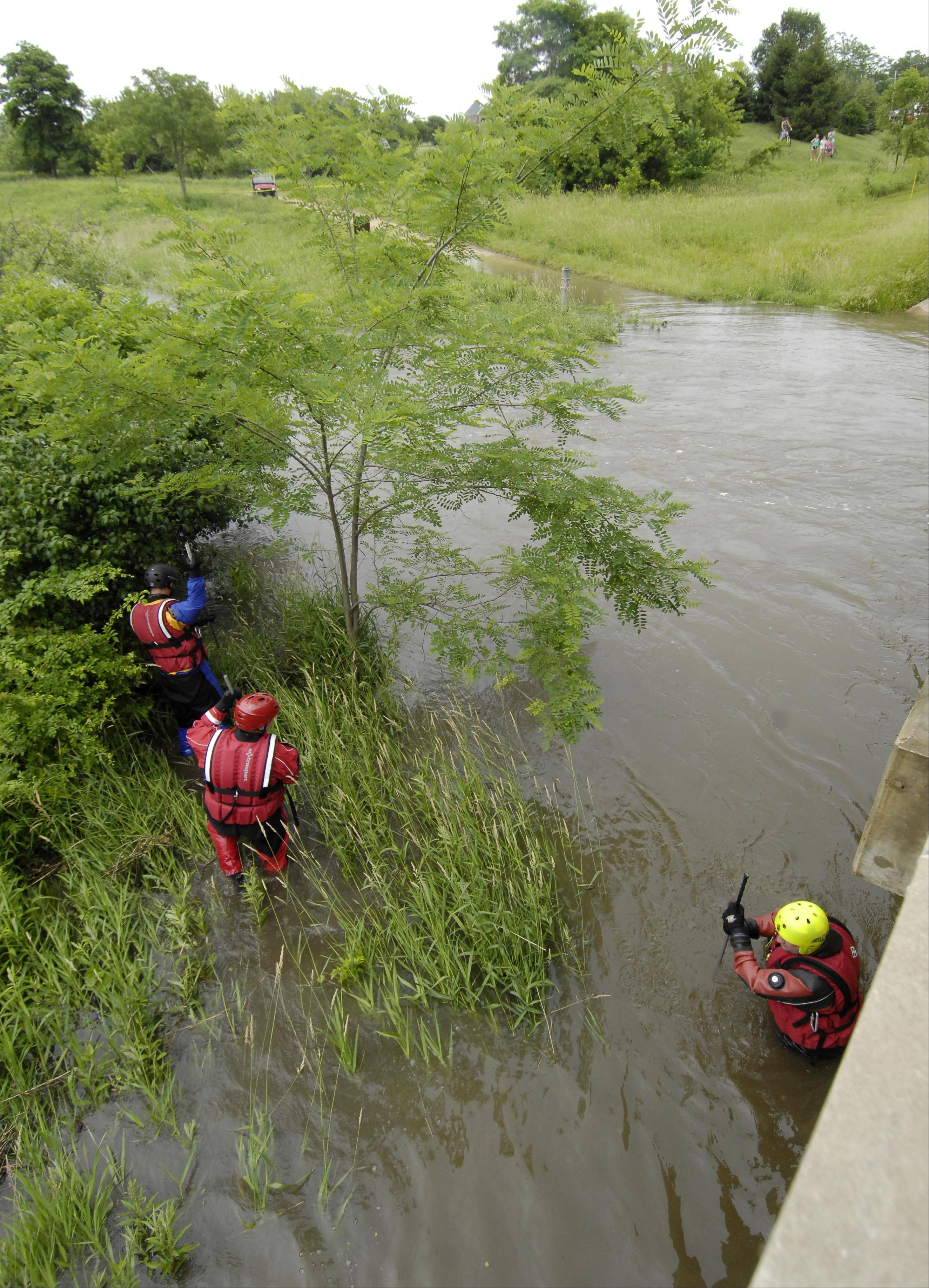 Rescuers look for a man and a dog who were reported swept away by a fast-moving creek in the Grassy Lake Forest Preserve near Lake Barrington.