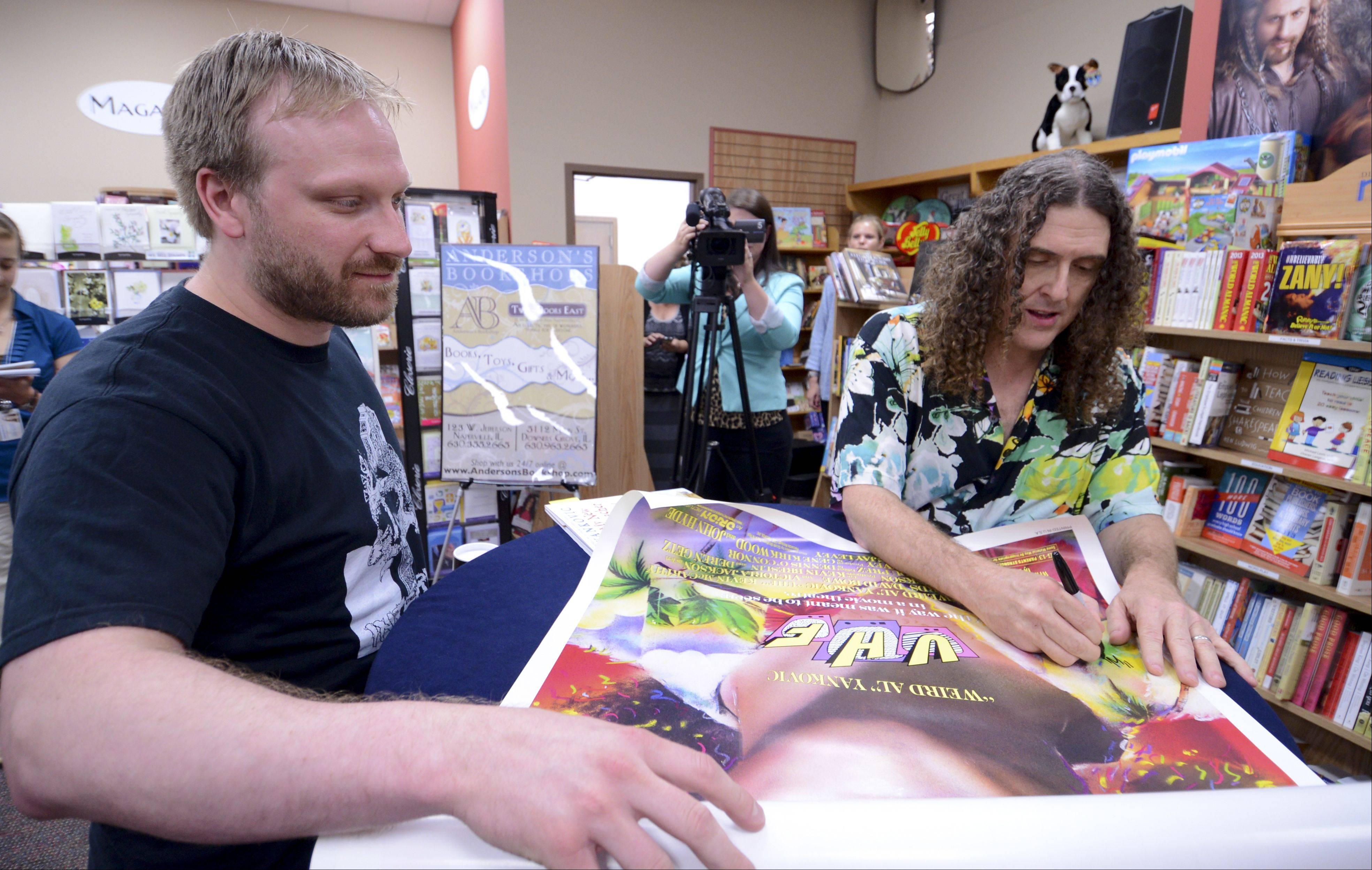 "Above, Clint Billington of Brookfield has Weird Al Yankovic sign a ""UHF"" movie poster during an event Wednesday to promote Yankovic's new children's book, ""My New Teacher and Me,"" at Anderson's Bookshop in Naperville."