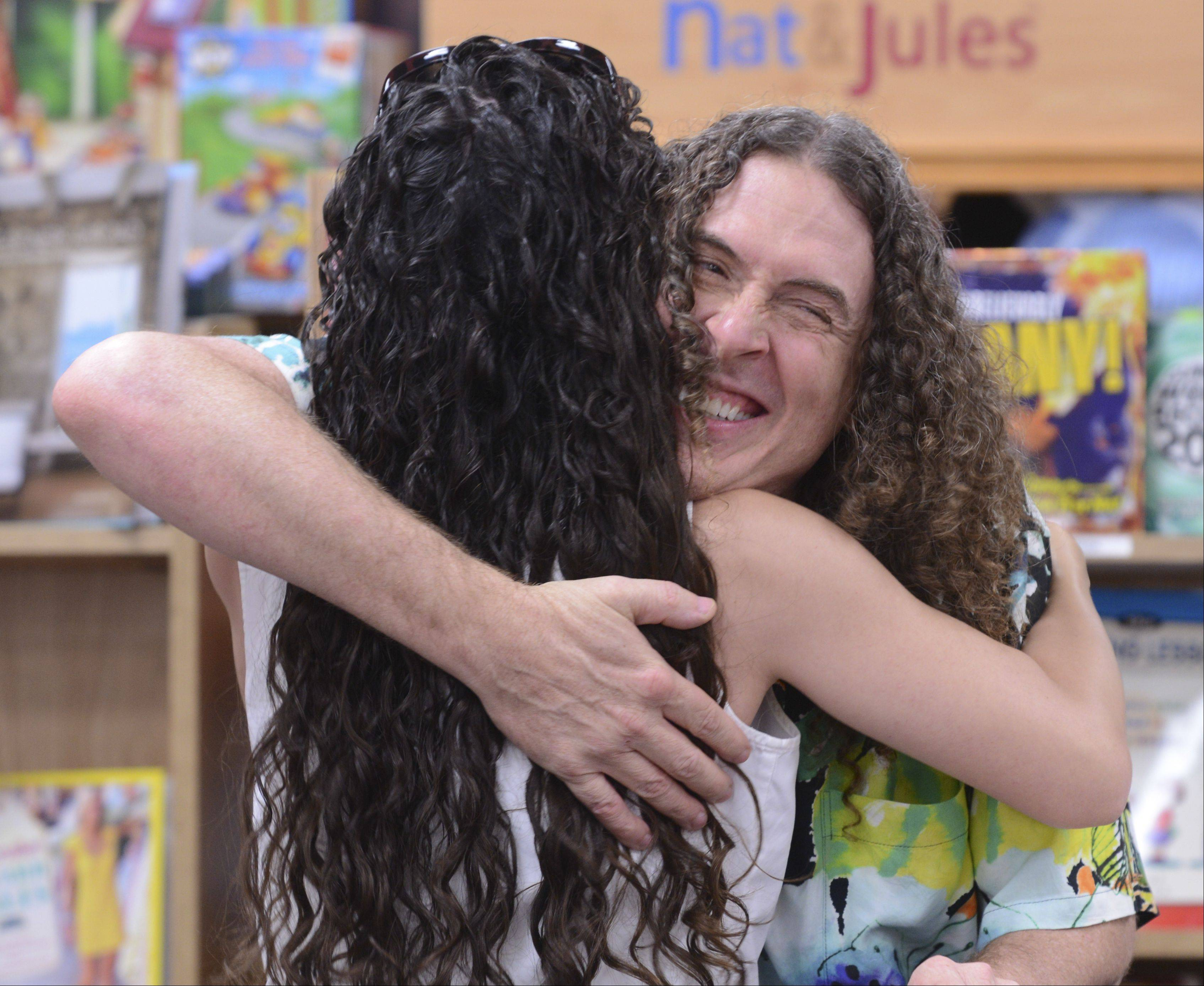 "Longtime fan Michelle Gargrave of Woodridge gets a hug from Weird Al Yankovic Wednesday during a book signing to promote his second children's book, ""My New Teacher and Me,"" at Anderson's Bookshop in Naperville."