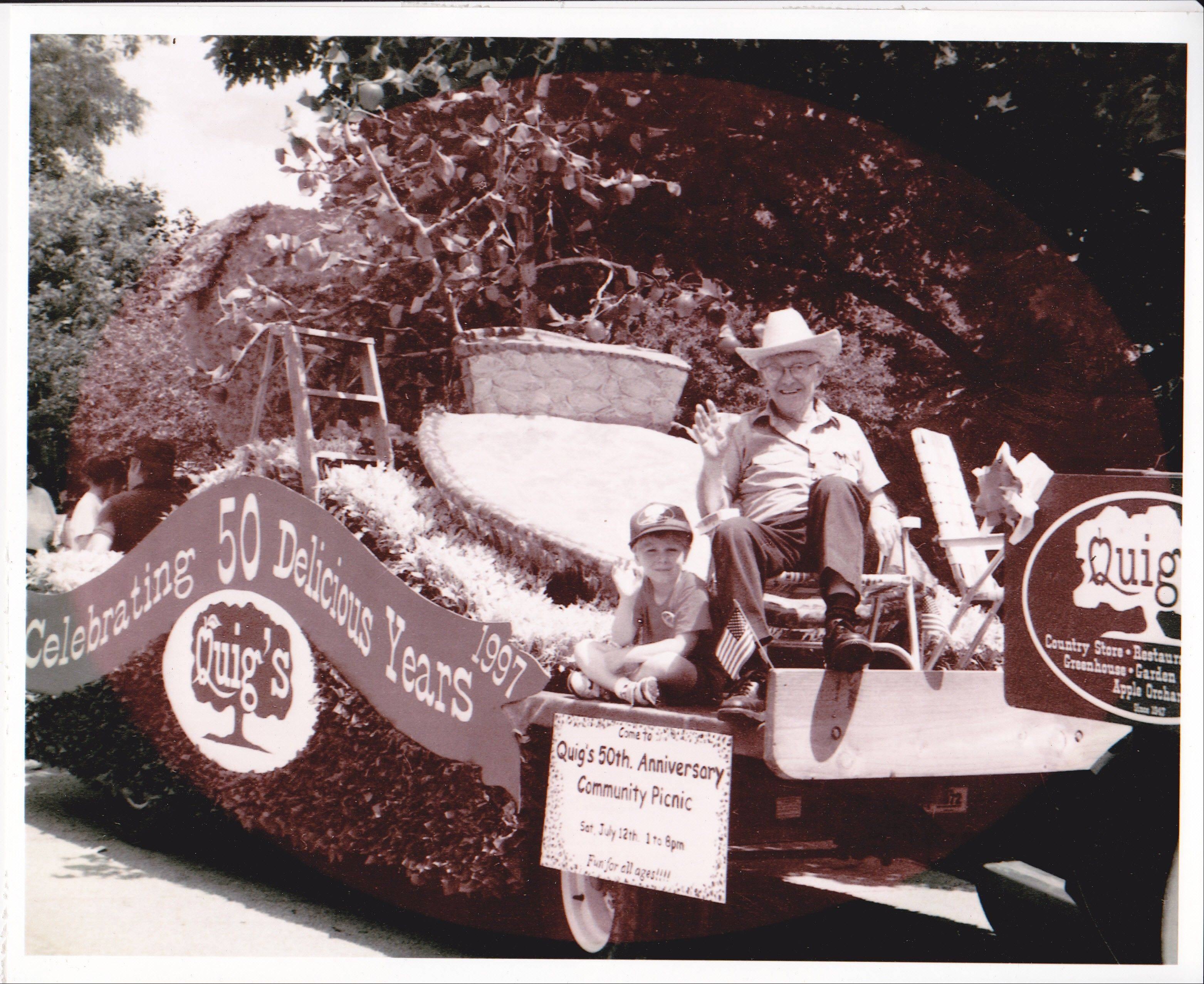 Robert Quig, founder of Quig's Orchard in Mundelein, rides a float in 1997 with his grandson Nathan in commemoration of the business' 50th anniversary. Quig, who died June 1, was known for his love of conversing with visitors.
