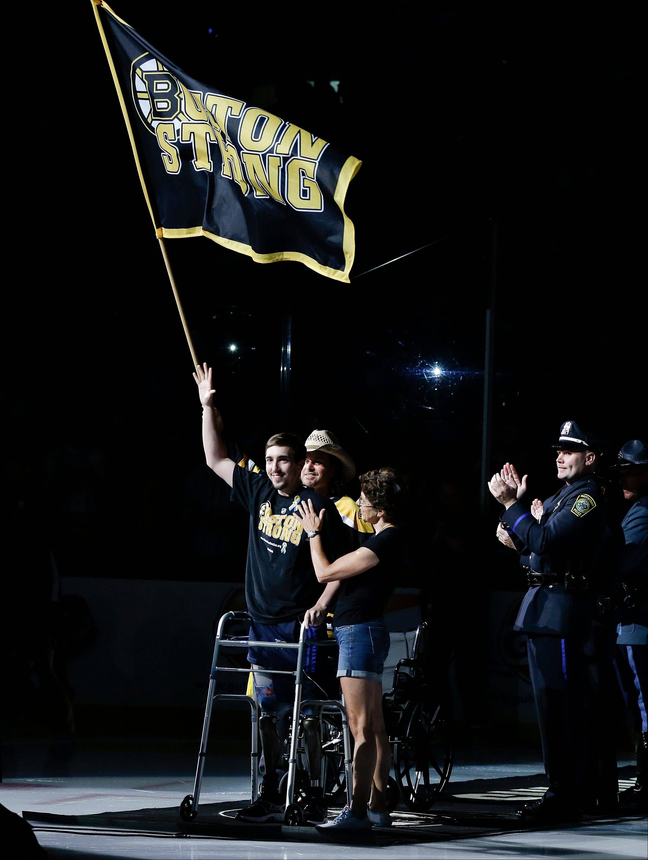 "Standing on artificial legs beneath a ""Boston Strong"" banner, Boston Marathon bombing victim Jeff Bauman waves to the crowd during an uplifting and emotional ceremony before Game 6 of the Stanley Cup Finals in Boston."