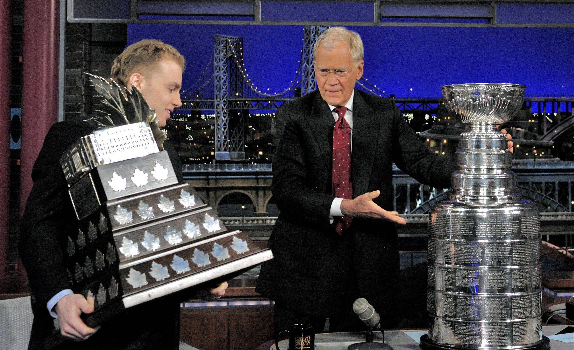 "Patrick Kane, hoists his MVP trophy while ""Late Show"" host David Letterman places the Stanley Cup on his desk during a taping of the show Wednesday in New York."