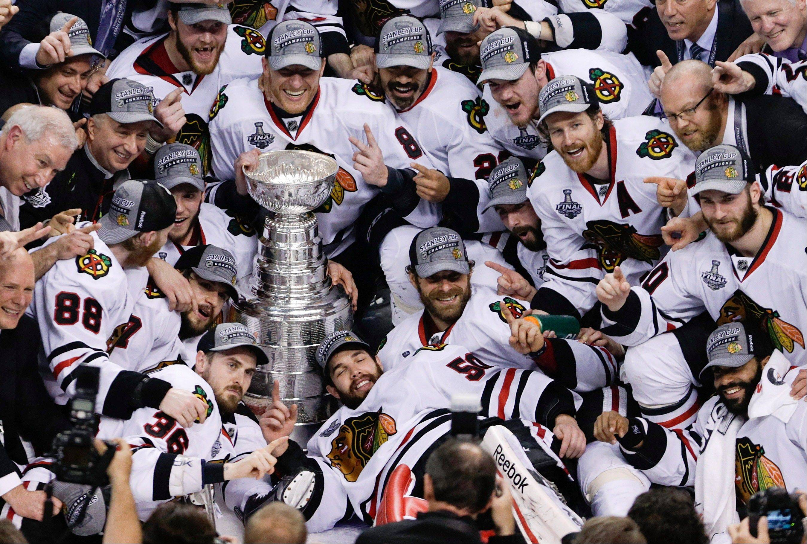 The Chicago Blackhawks pose with the Stanley Cup after beating the Boston Bruins 3-2 in Game 6 of the NHL hockey Stanley Cup Finals, Monday, June 24, 2013, in Boston.