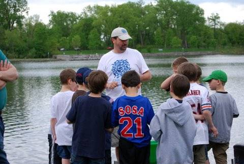 Johnny teaches a group of Cub Scouts on the water's edge as they get ready to catch a bunch of fish from a local pond.